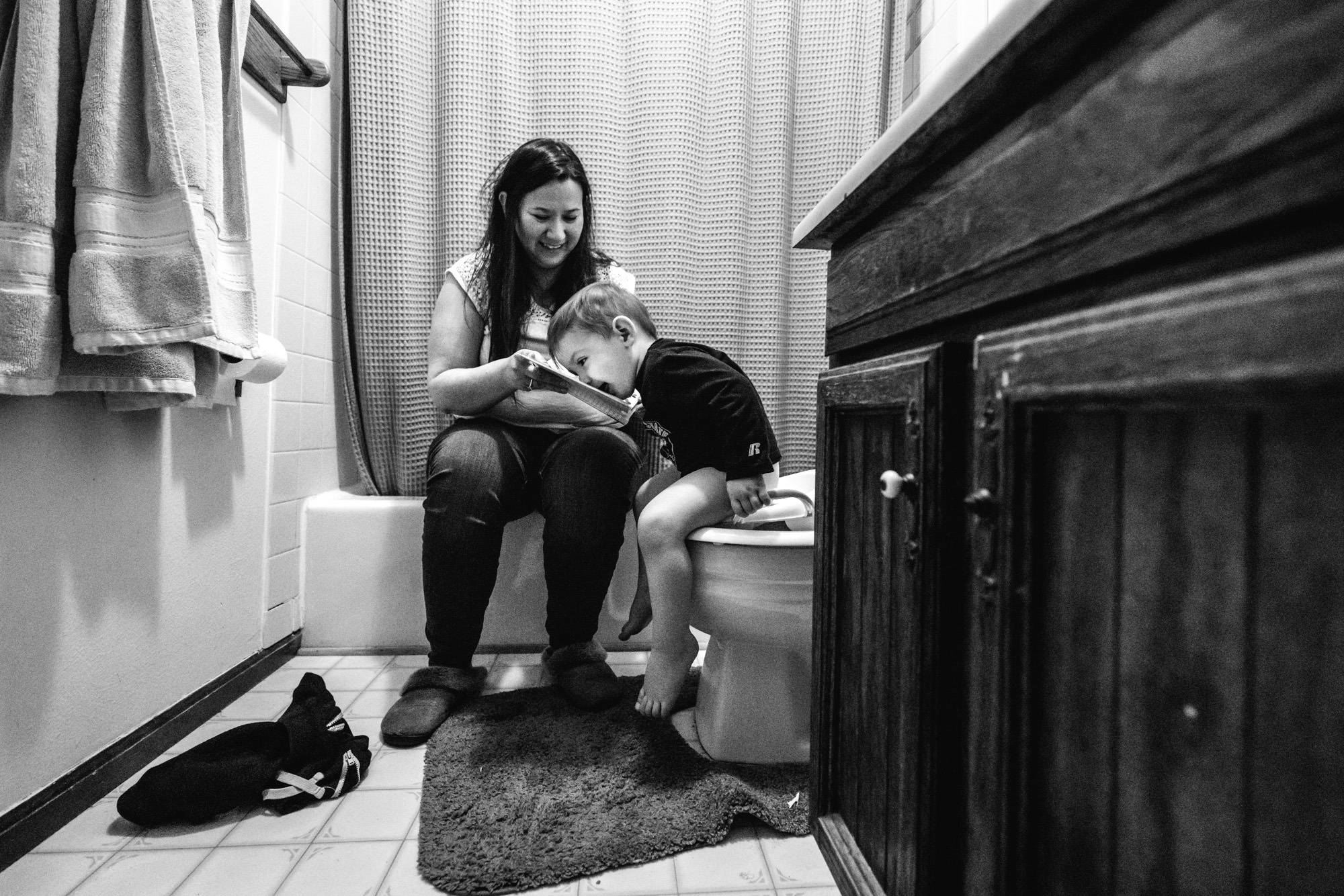 Mother sits in the bathroom with her toddler son as she tries to potty train him. She holds a book up for him that he is licking.
