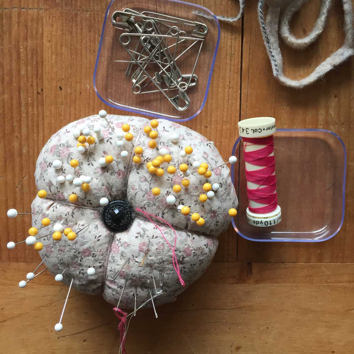 Pin cushion, thread and pins for making hooked rugs