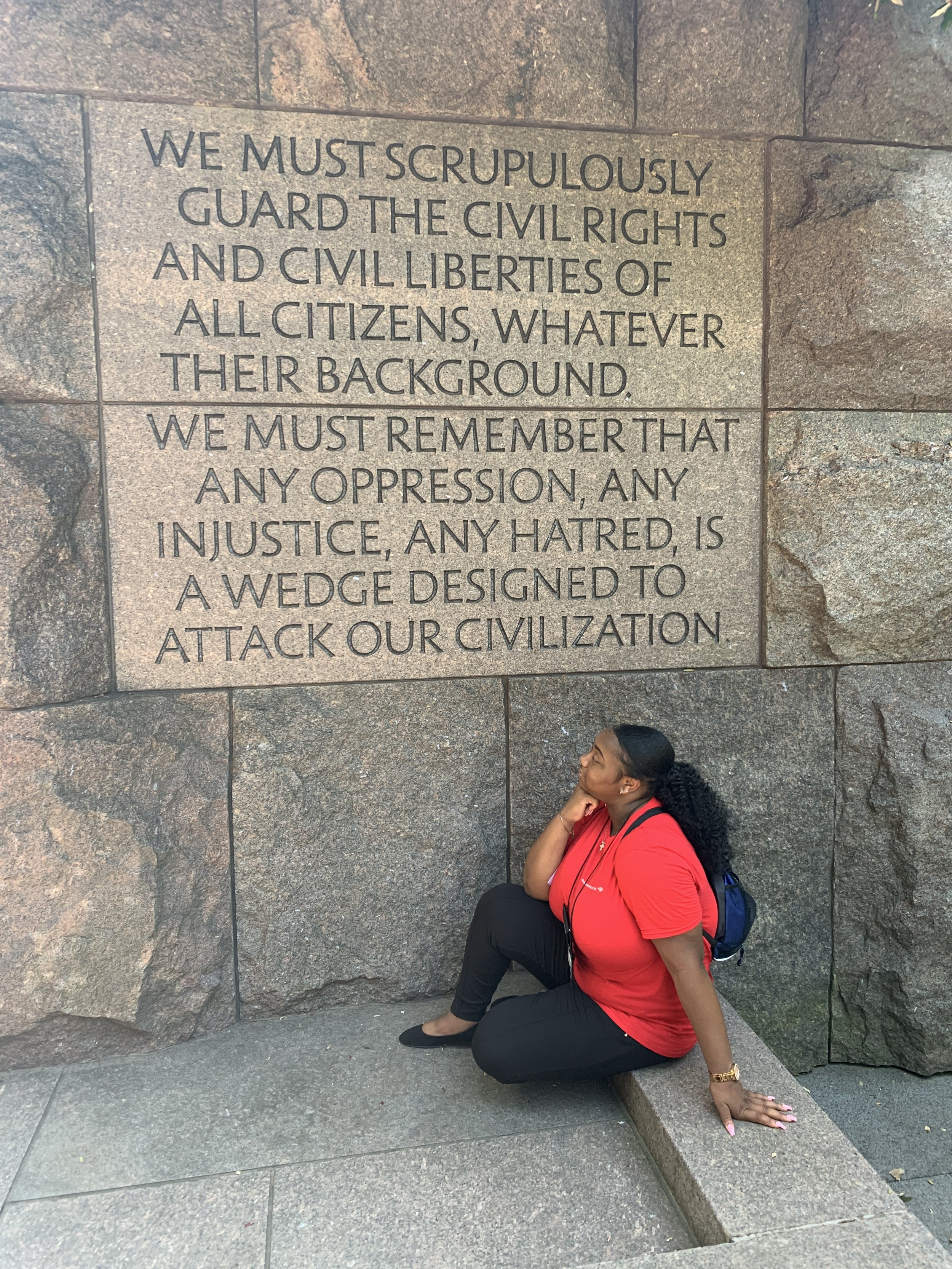 Jasmin in front of a quote on guarding civil rights and liberties, at the FDR memorial in Washington, D.C.
