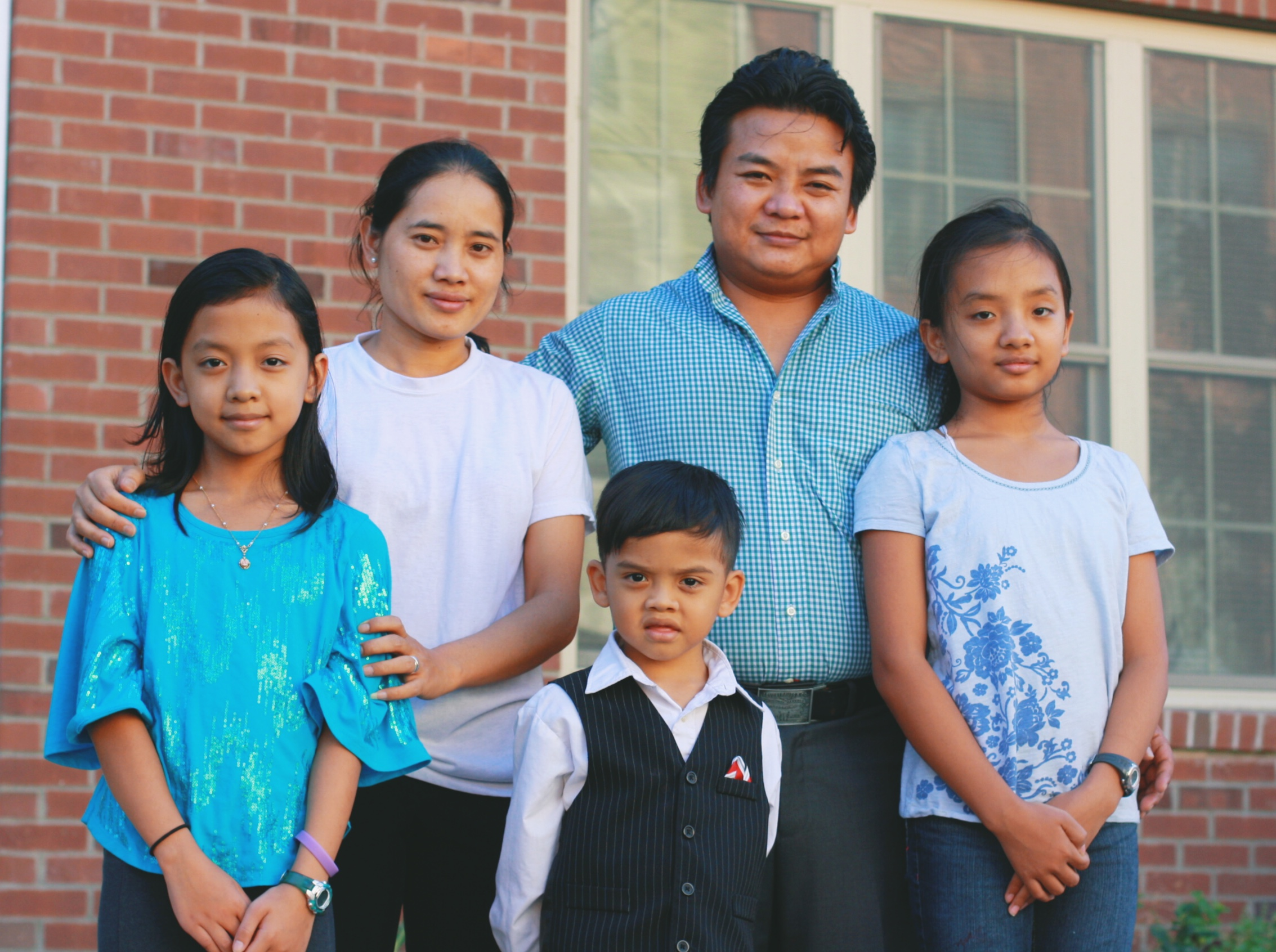 Homeowner Khoon Lin and his family outside their Habitat home. Your support helps more families like Khoon Lin's find stability here in our community.
