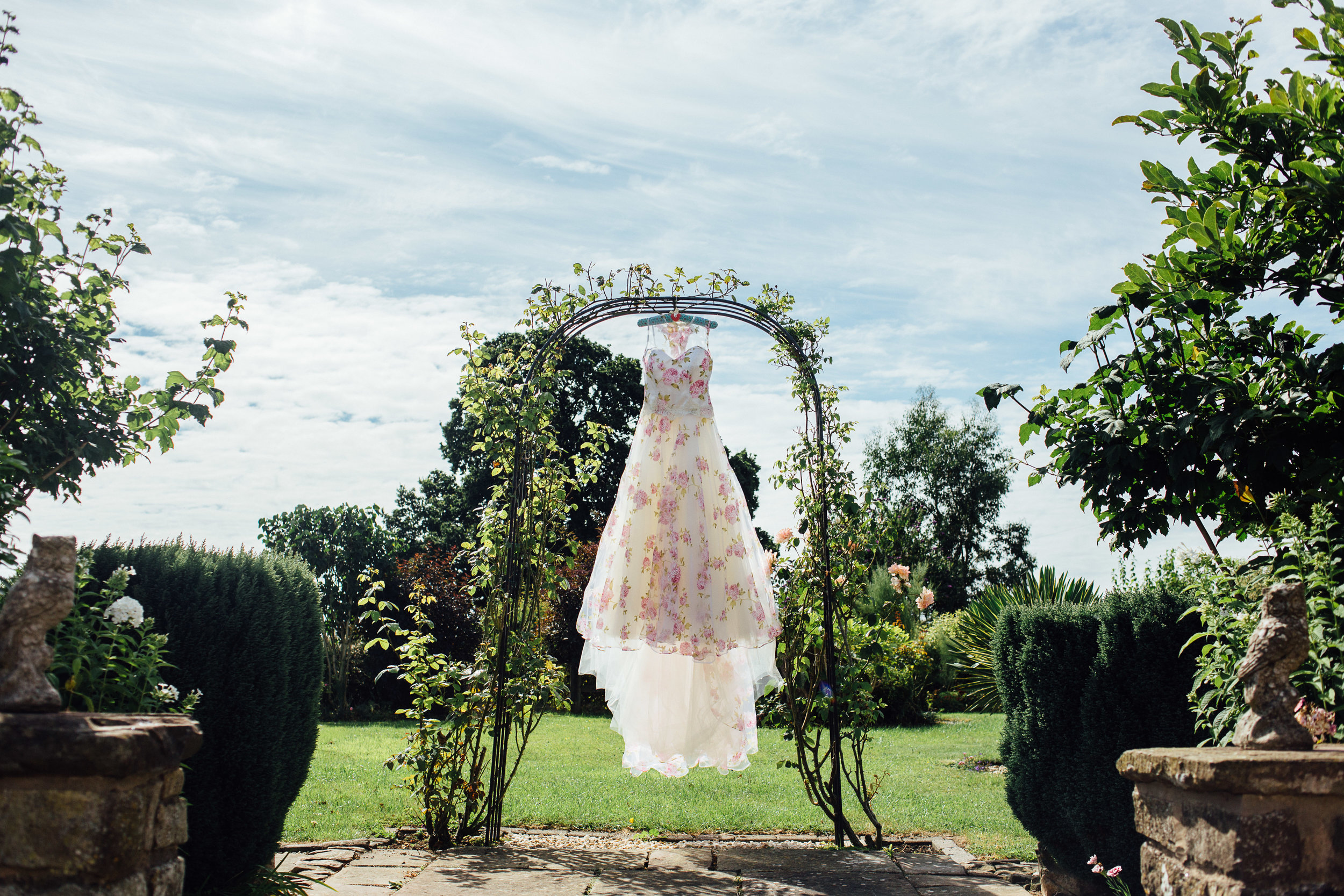 floral wedding dress hung in arch - gloucestershire wedding photographer