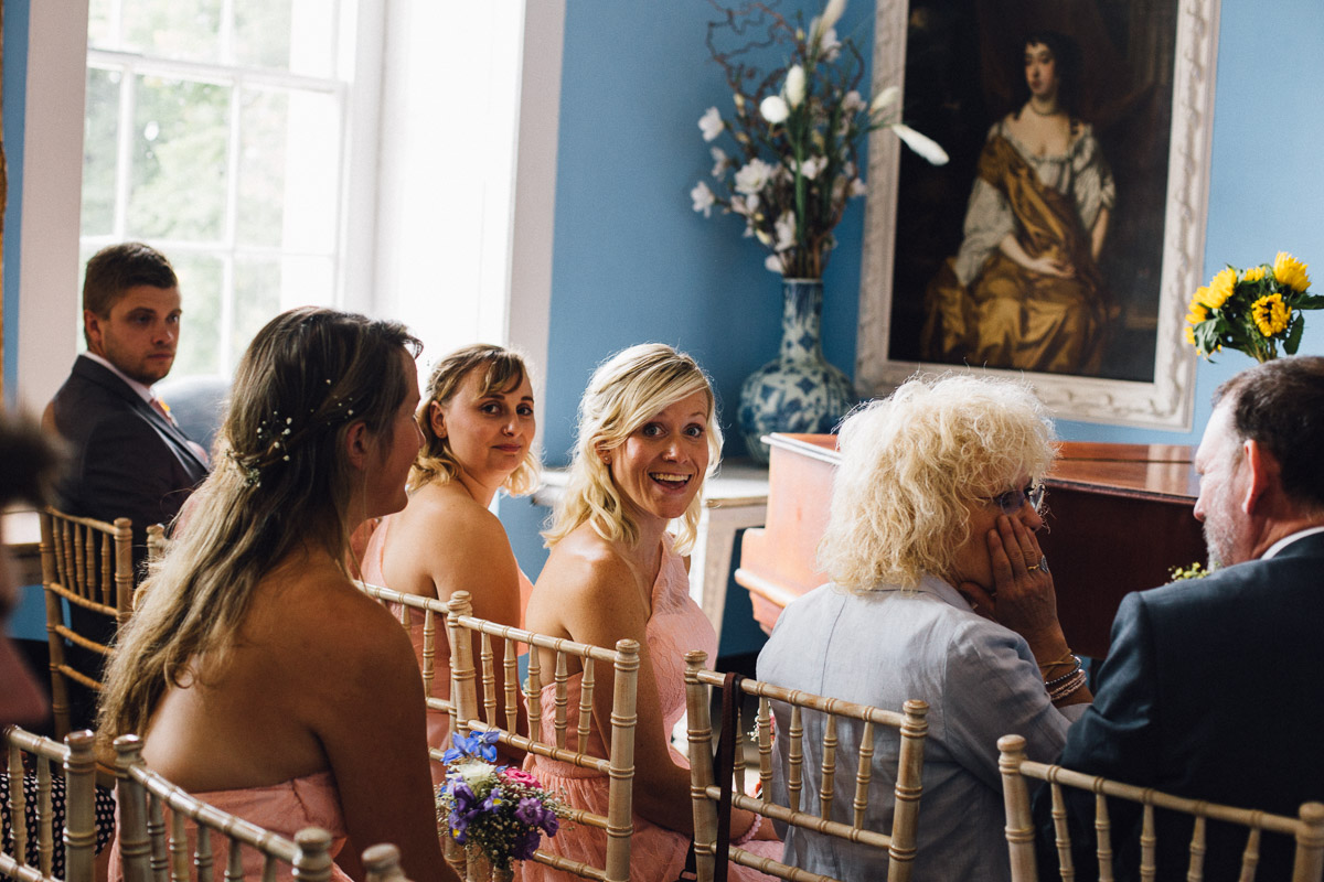 Bridesmaids laughing whilst Bride and Groom Sign Register