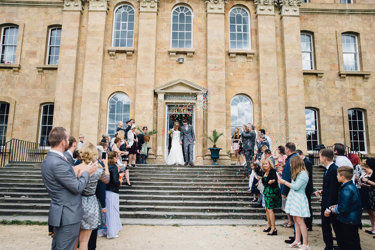 Guests Throw Confetti over couple on Steps at Kings Weston House