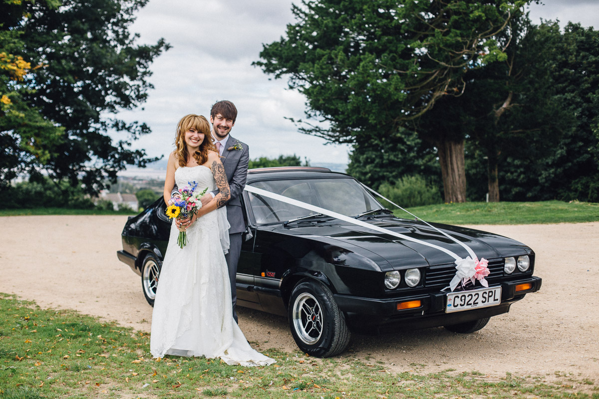 Couple Pose by Alternative Wedding Car outside Kings Weston House