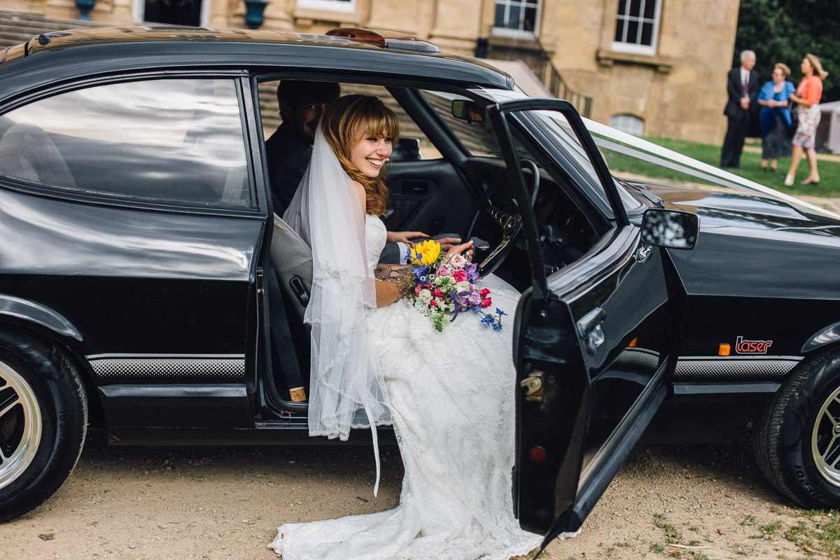 Bride Sitting in Wedding Car Kings Weston House