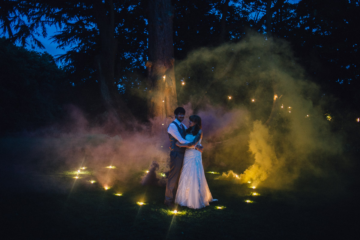 Alternative Couple portrait at night in Festoon lights and Yellow and Purple Smoke Bomb