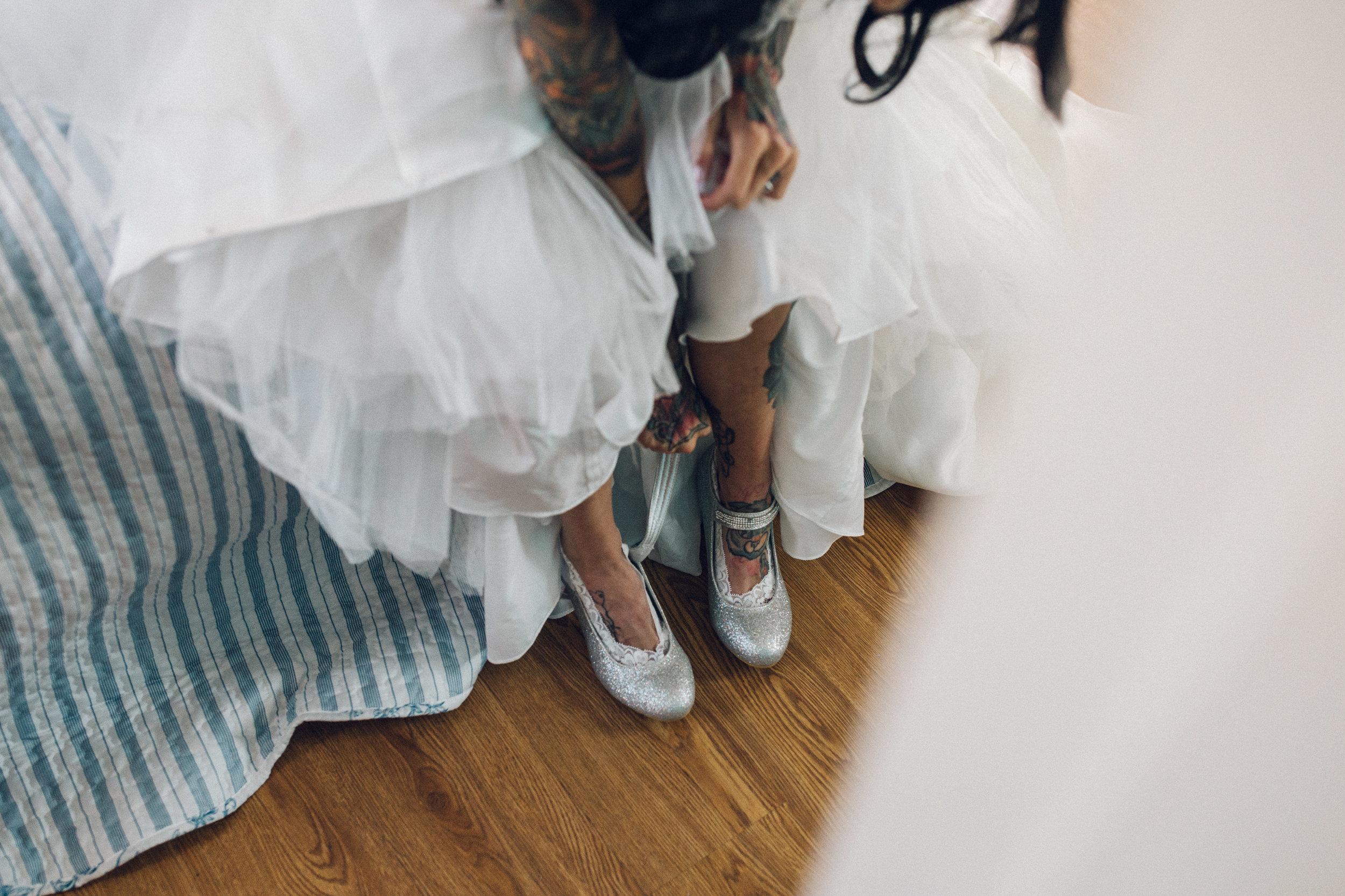 Heavily tattooed bride putting dress on
