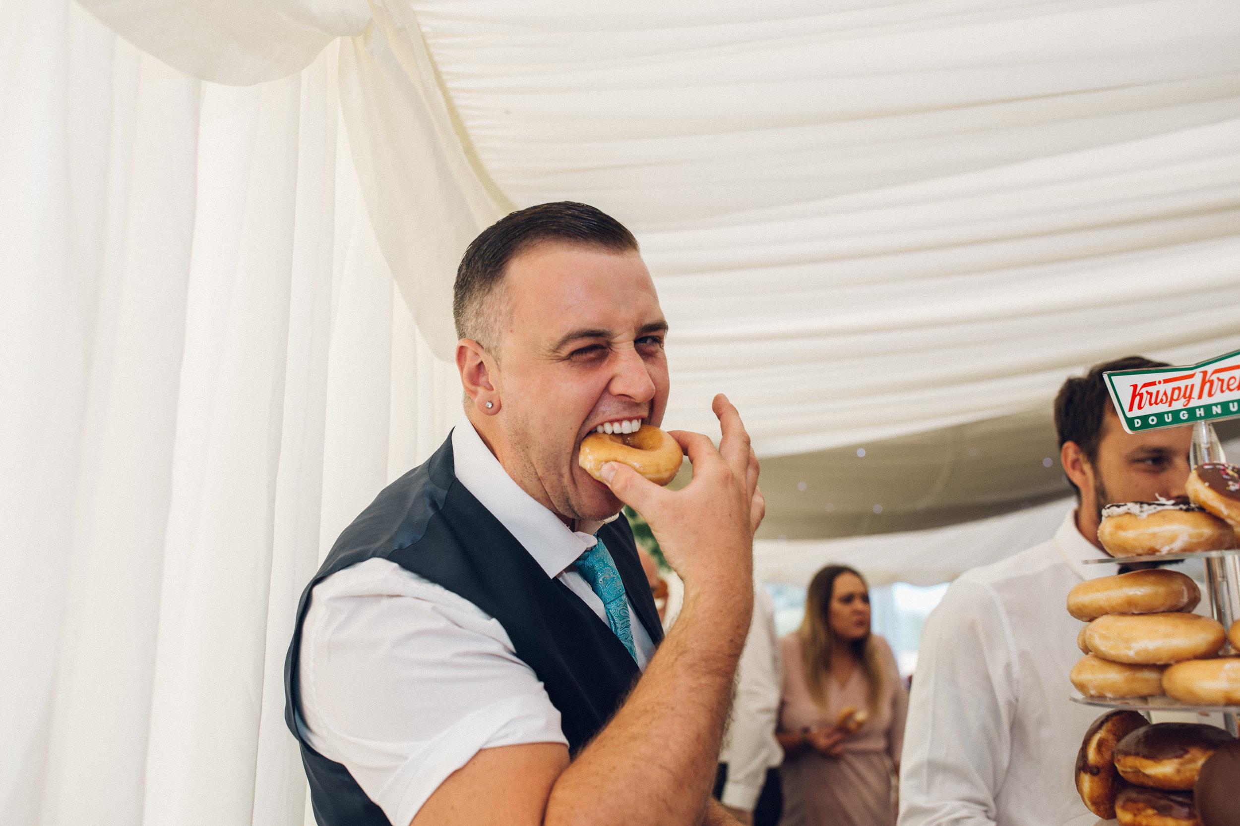 Wedding Guest eating Krispy Kreme Doughnut wedding cake Zinnia Garden