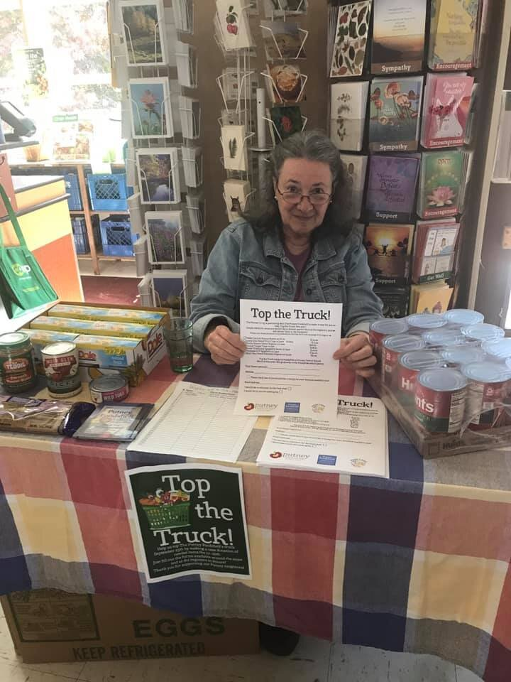 Board President, Nancy Olson mans the table at the Putney Co-op where folks could order cases of food at bulk rates for the Foodshelf.