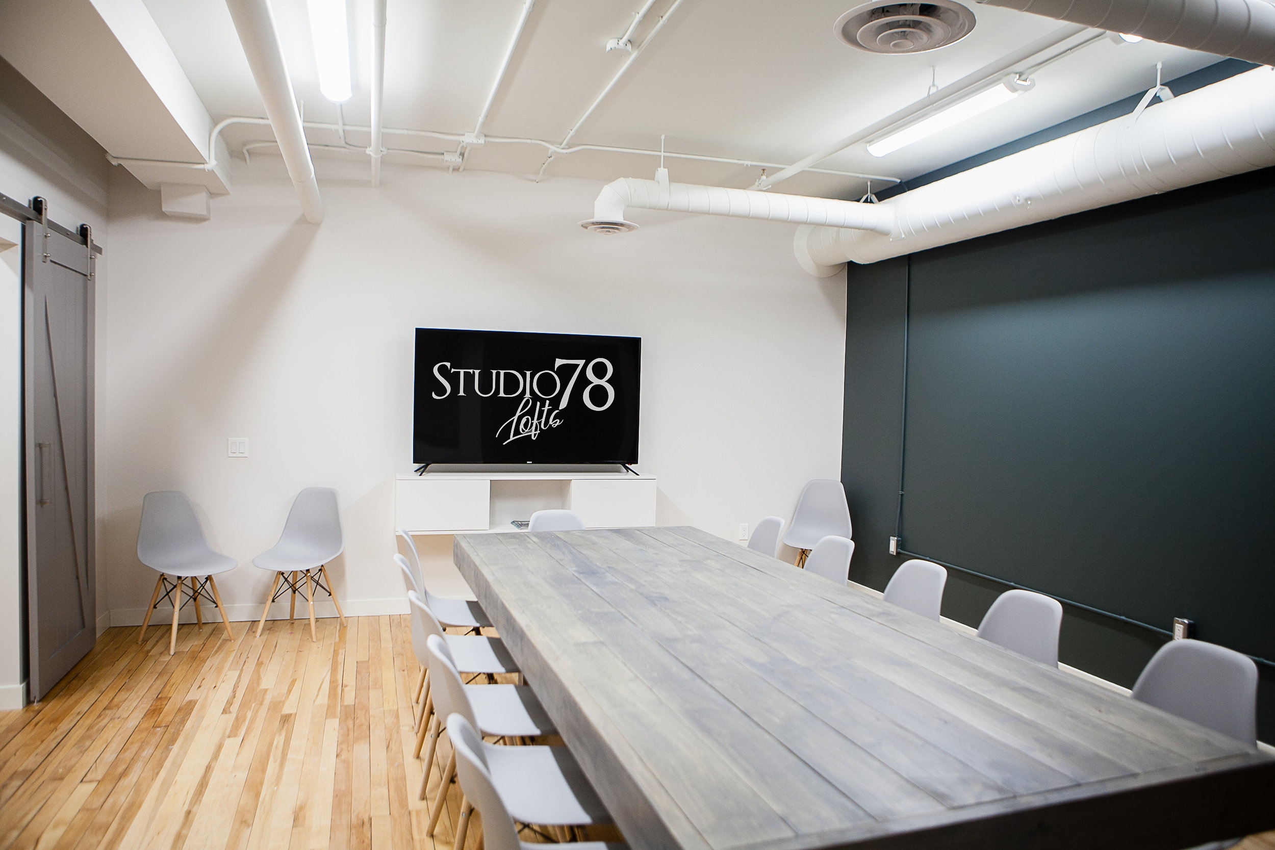 "Small Boardroom - The Layout for the Small Boardroom is 16' deep by 22' wide. Ideal for up to 10-12 people. Featuring 65"" TV with Wifi and whiteboards for meetings. Offering coffee and snacks catering services, to appetizers and beverages for evening meetings and workshops."