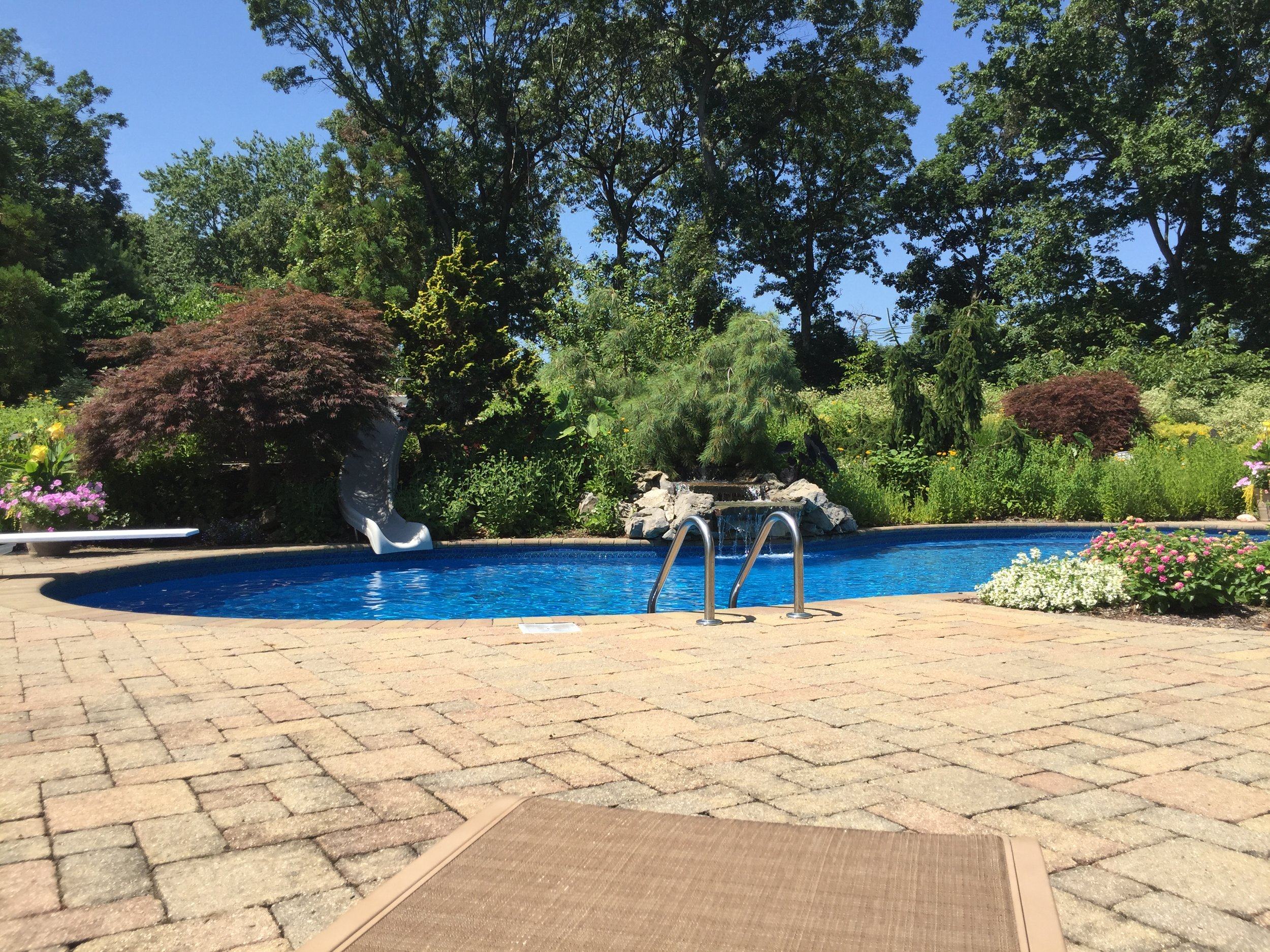 Top landscape design company with pool waterfallin Long Island, NY