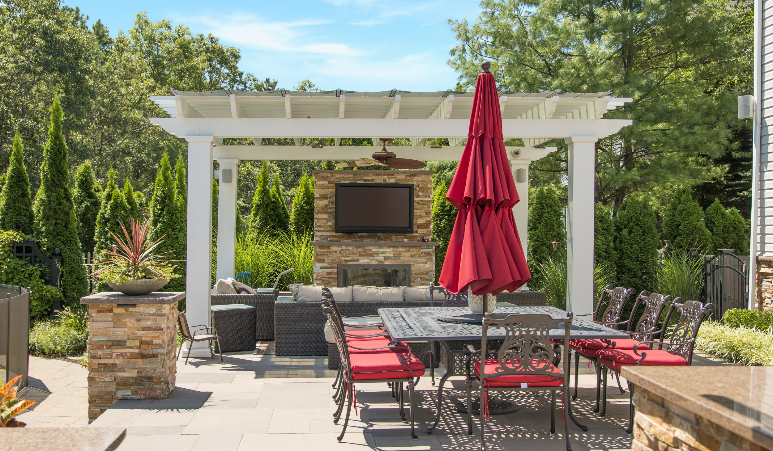 Landscape design with techo-bloc stone fire feature in Long Island, NY
