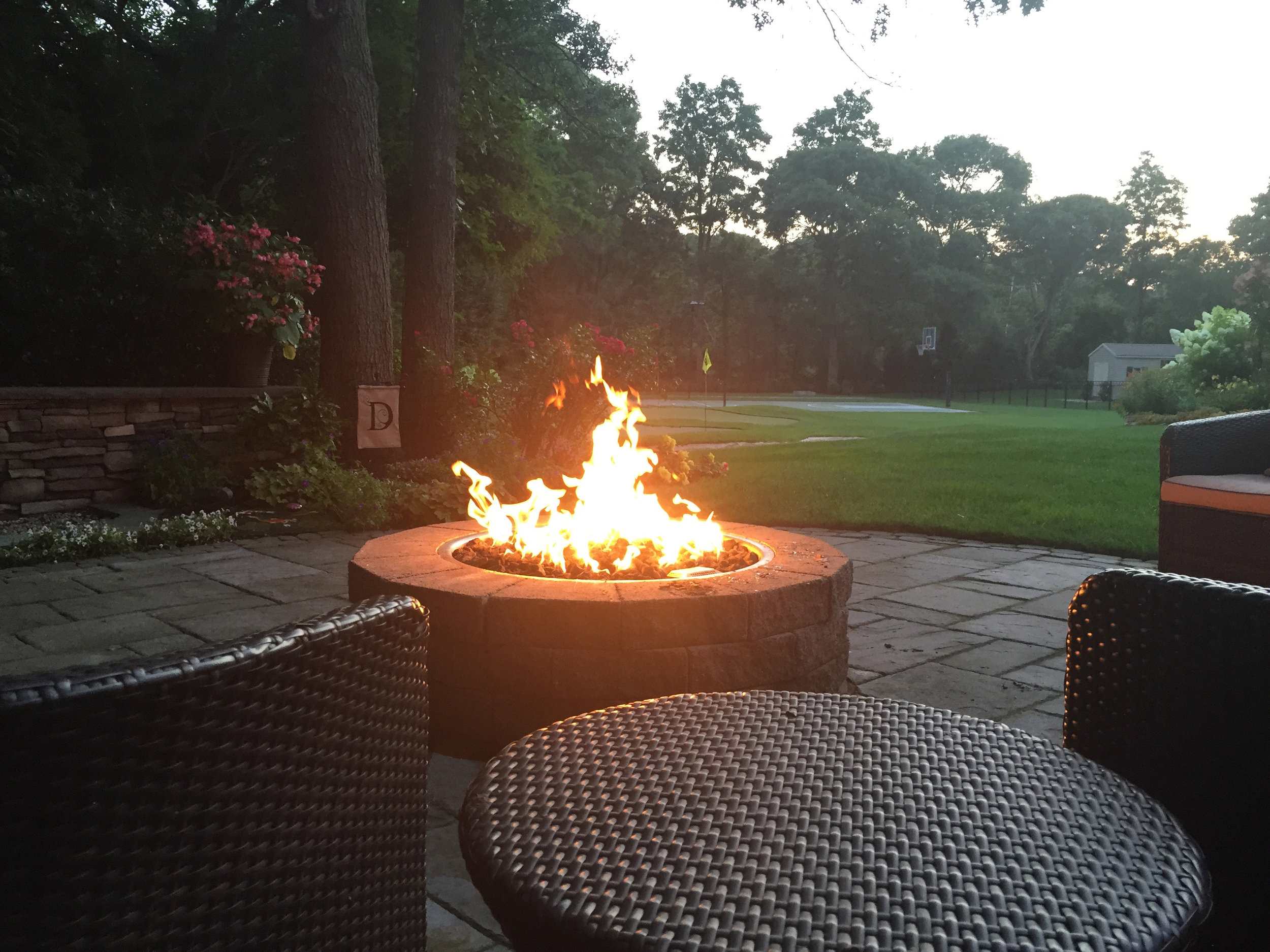 Top landscape design with a natural stone fire pit in Long Island, NY