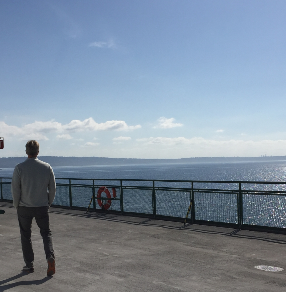 Man on deck of ferry with Puget Sound in background.
