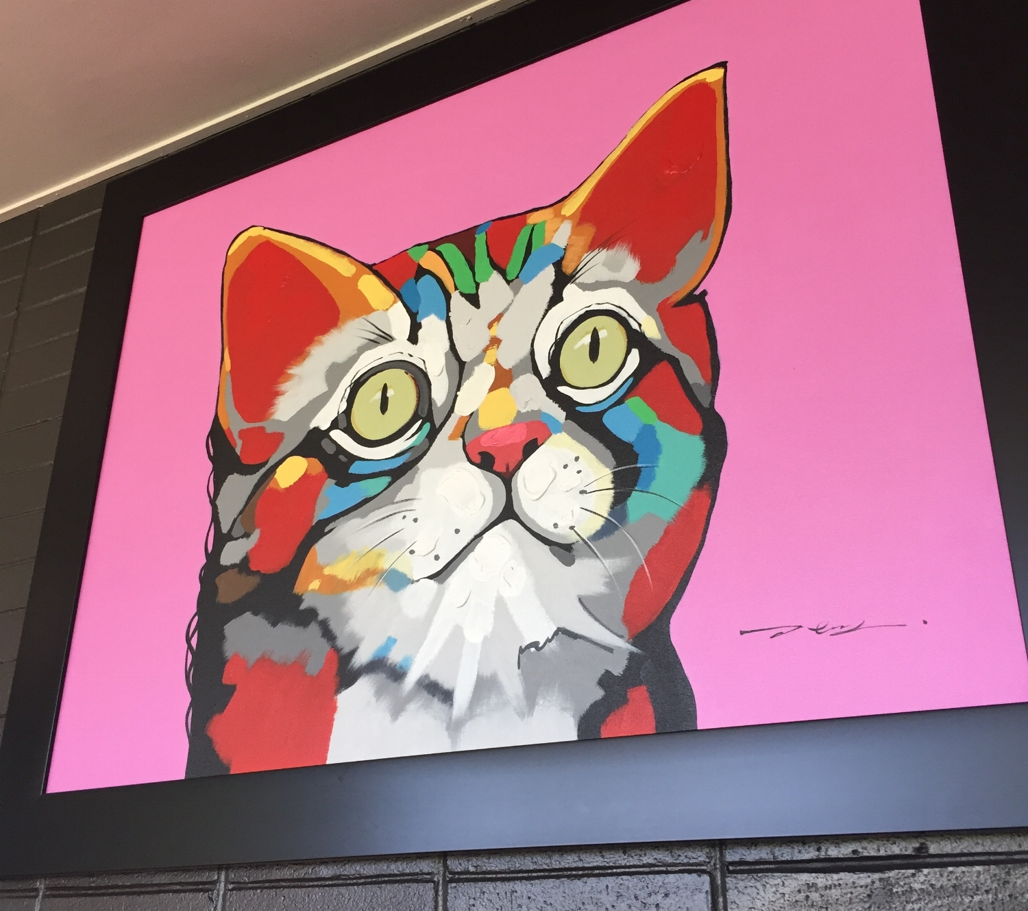 Framed painting of a cat in bright colors and a pink background.