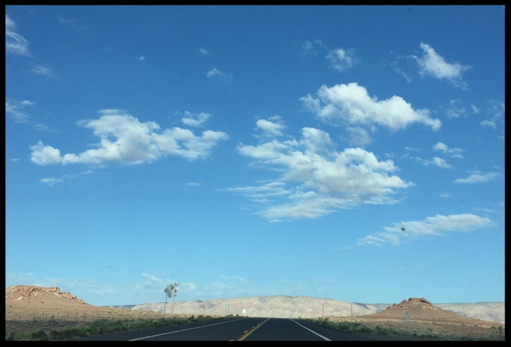 A road from driver's perspective with blue sky and  clouds