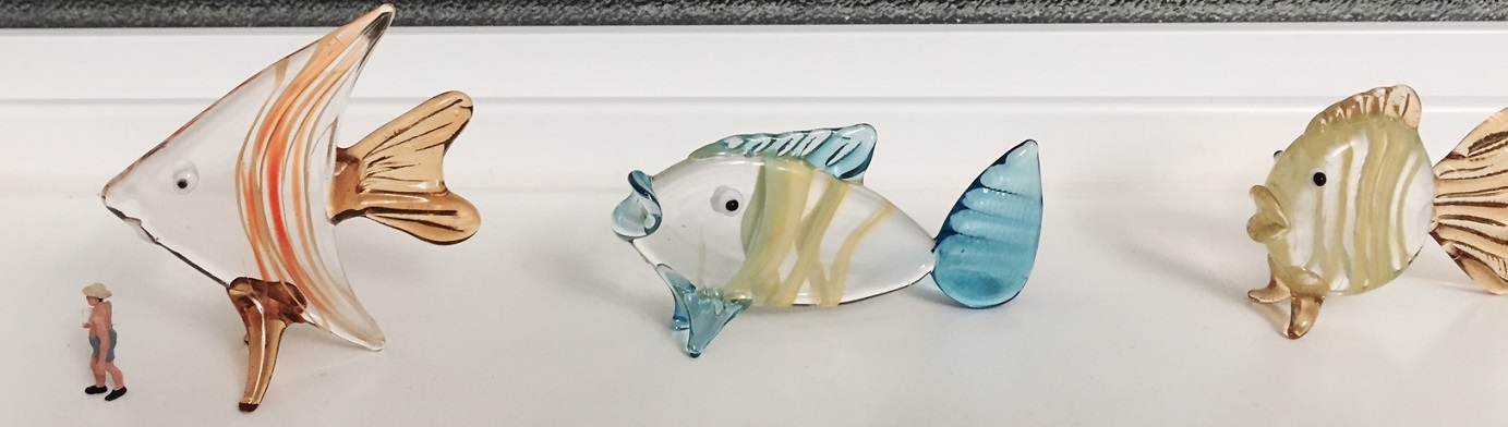 Miniature of a man walking in front of some glass fish ornaments.