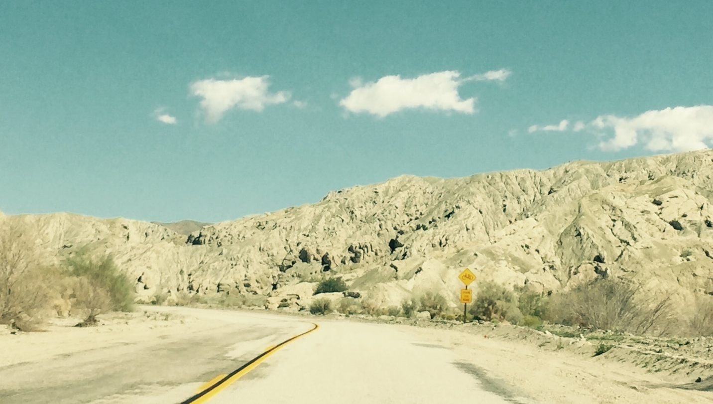 A road with yellow line through middle, going through desert rock.