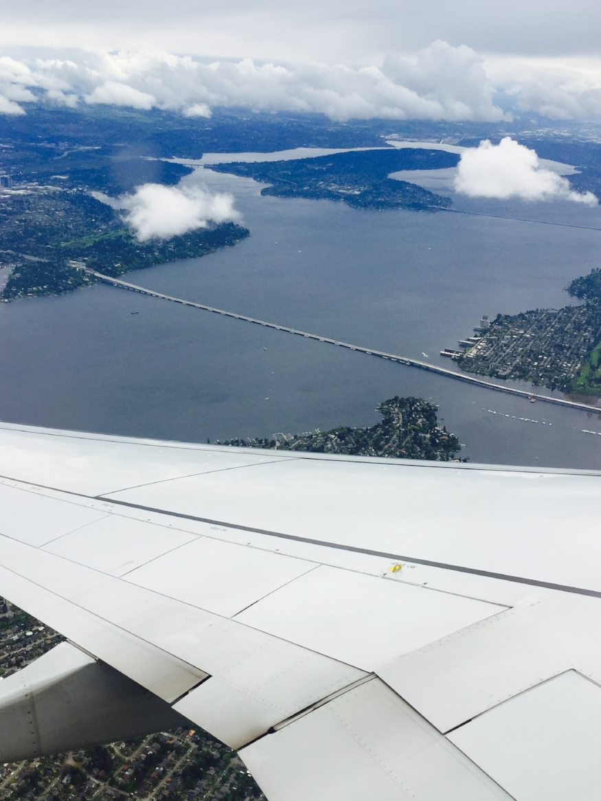 Airplane wing over islands and lake and a floating bridge.