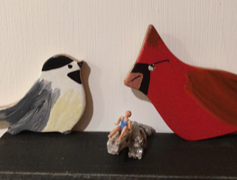 Image of two wooden birds and a tiny person in the middle.