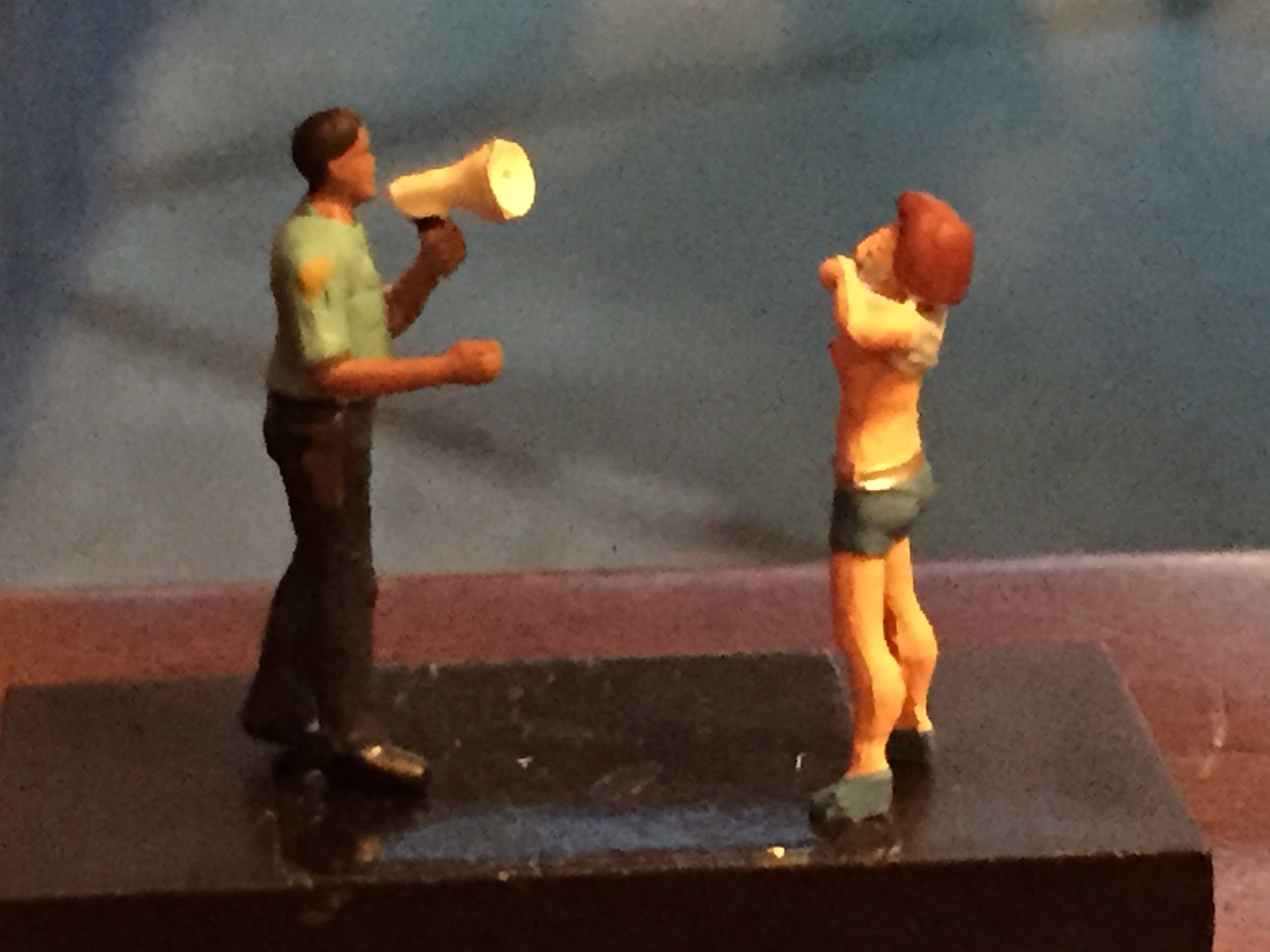 Miniature figures of a police with a horn and a woman pulling up her top