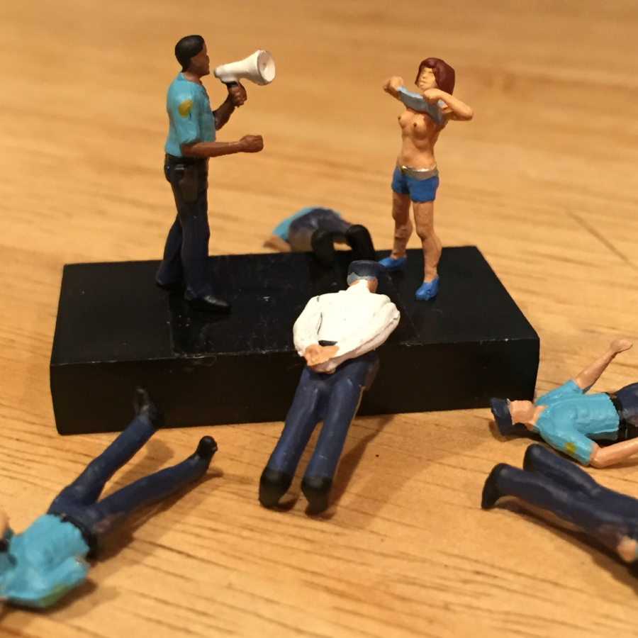 Miniature figures of a cop with a horn, a woman flashing and downed cops.