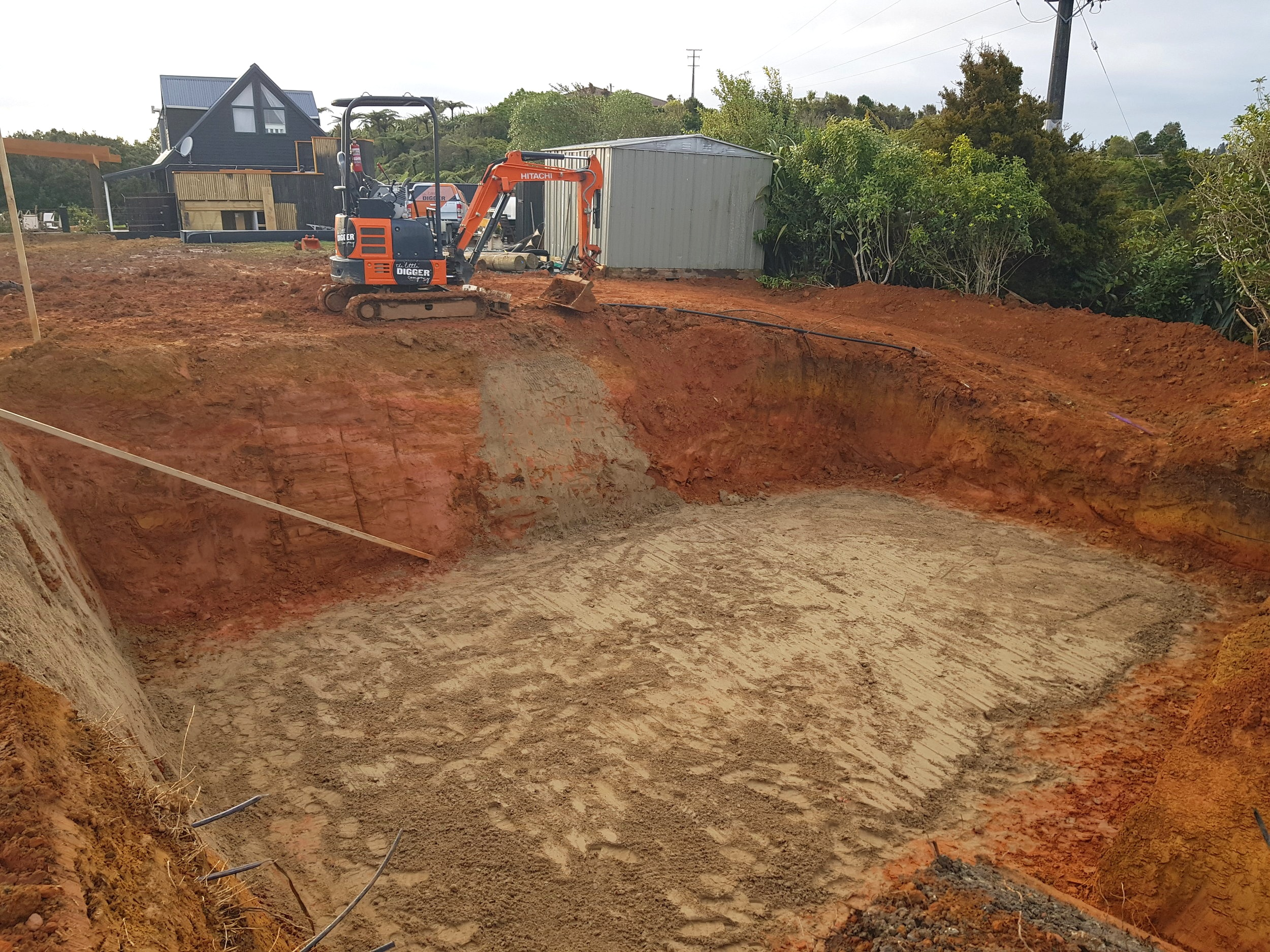 Matakana   The job was to create a space for 2x  30,000L water tanks.  The challenge was not to get stuck in the hole. How was it done? By building a track to access the pit.