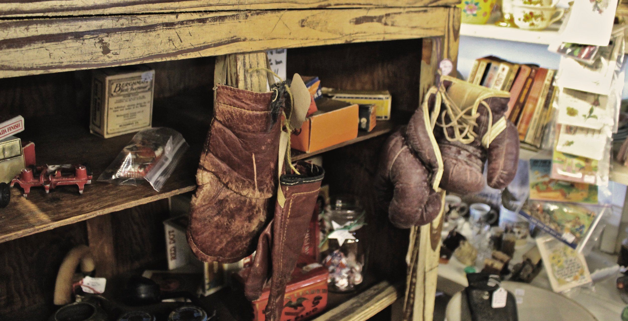 Worn boxing gloves hang as antiques from the cabinet