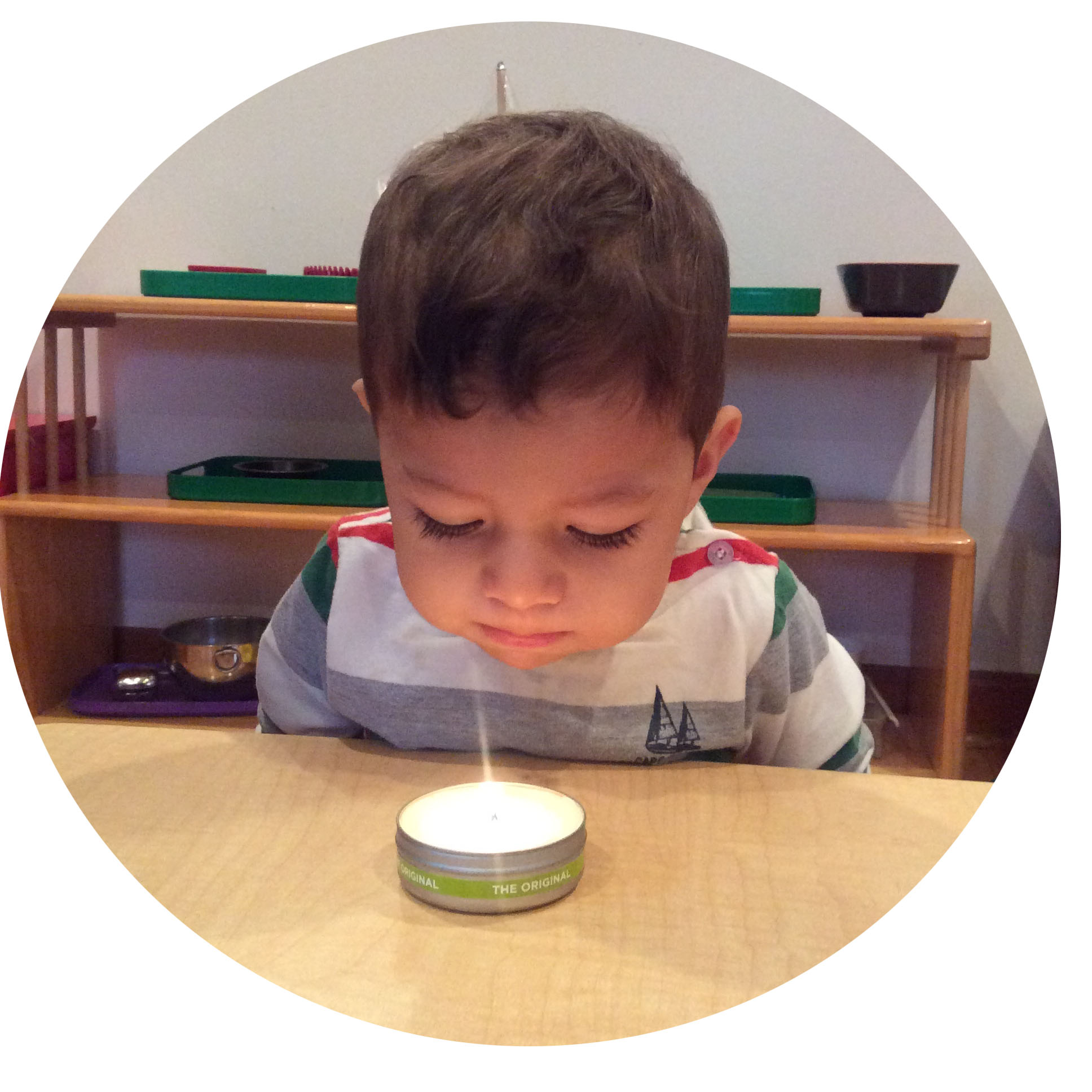 A toddler learns how to use breath to gently blow out the candle.