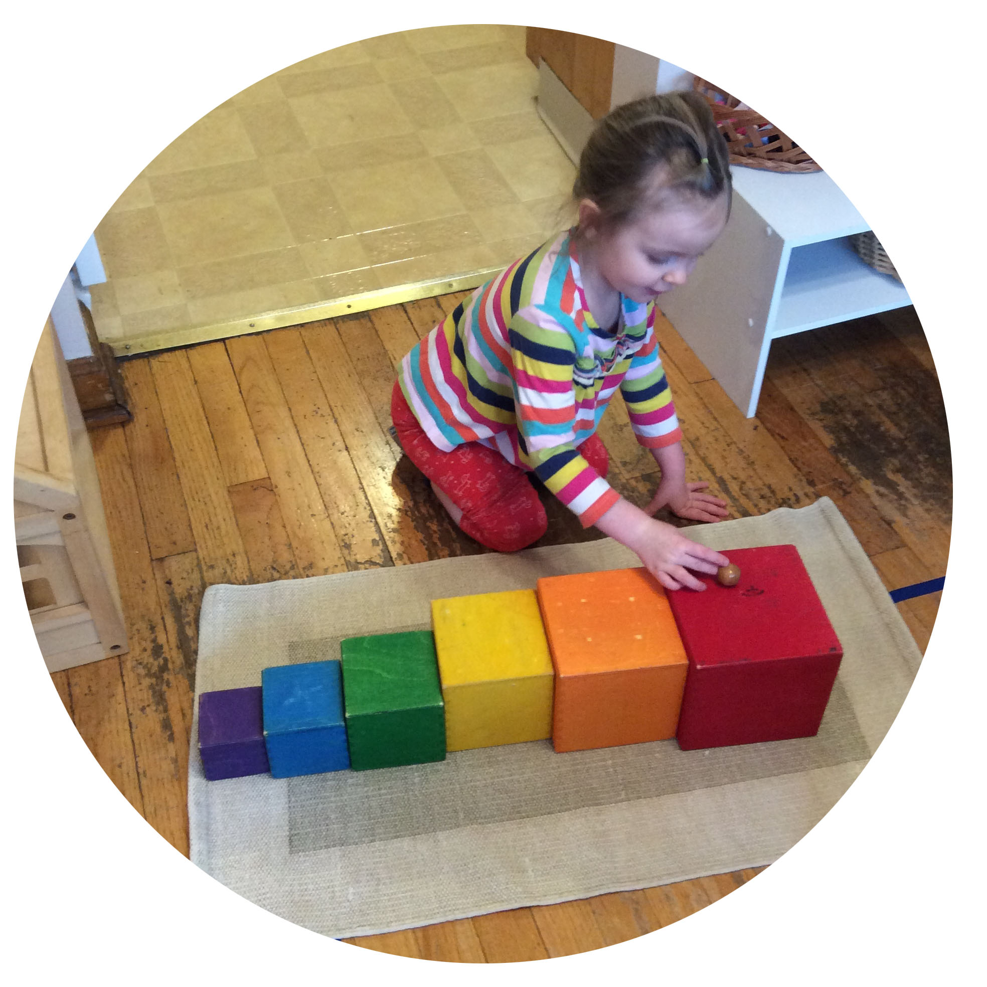 """Children are encouraged to explore shape and size to learn basic concepts of geometry. Here, we see a curious student practicing rolling the marble down the """"steps."""""""