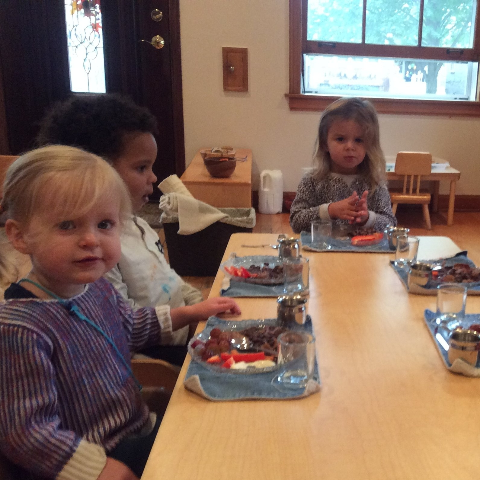Children in both toddler and primary classrooms eat their meals at the table with a full table setting.