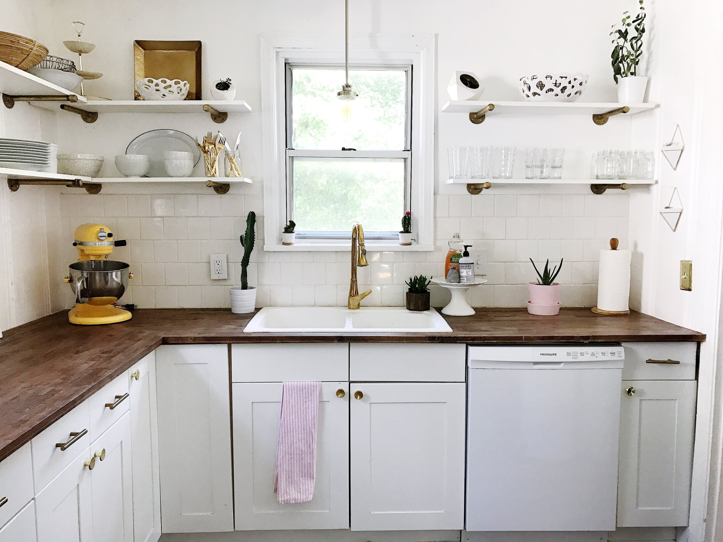 We loved the idea of open shelving. We are trying to adapt to a minimalist lifestyle, so we didn't need much cabinet space. We made our shelves out of galvanized pipe that we sprayed gold, and white pre-treated wood.
