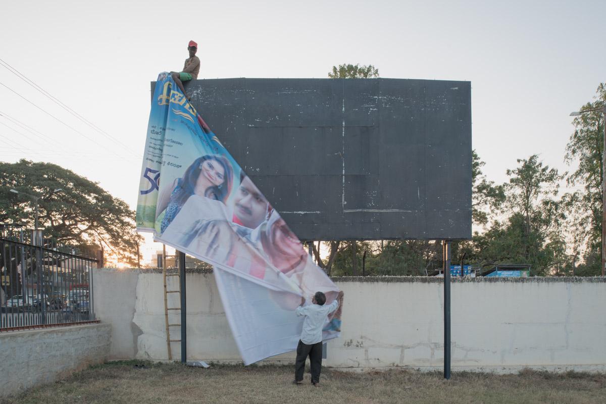 Putting up a poster at Nanda theatre, Mandya.