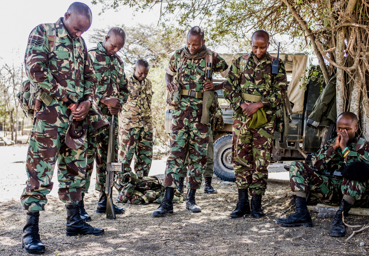 NPR (National Police Reservists) have a moment of prayer before they go out on an overnight patrol of Ol Pejeta conservancy in Central Kenya.  The armed men patrol the 360 km2 (140 sq mi) not-for-profit wildlife conservancy around the clock and protect the rhinos and other animals from deadly poachers.