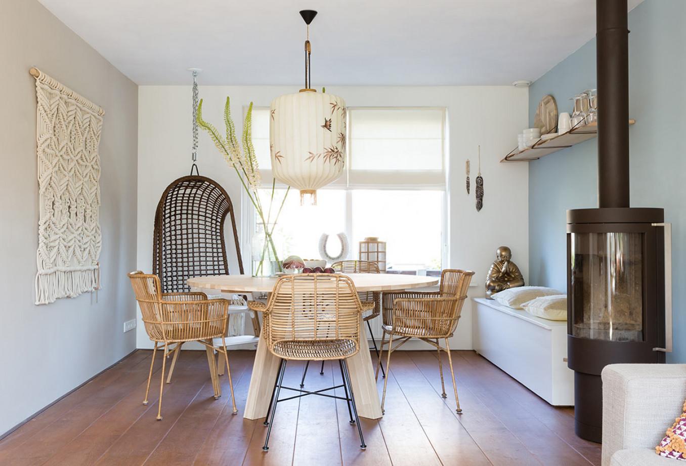 eethoek-blauw-rotan-hangstoel-houten-eettafel-rond-wandkleed-haard.jpg