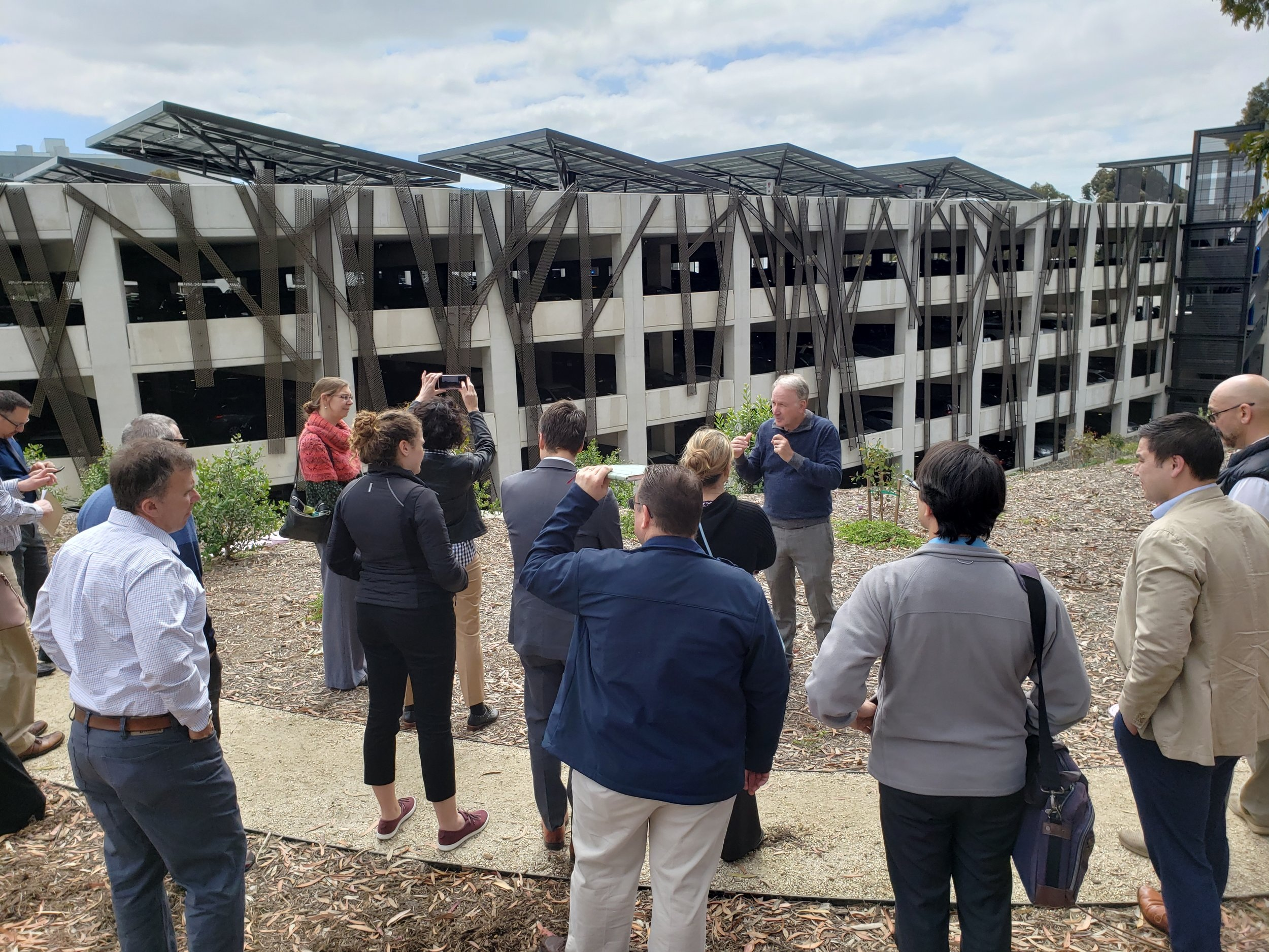 Dr. Byron Washom explains the value of mounted solar arrays, vehicle charging infrastructure, and their connection with the UCSD microgrid to the MERC Cohort at this parking facility.