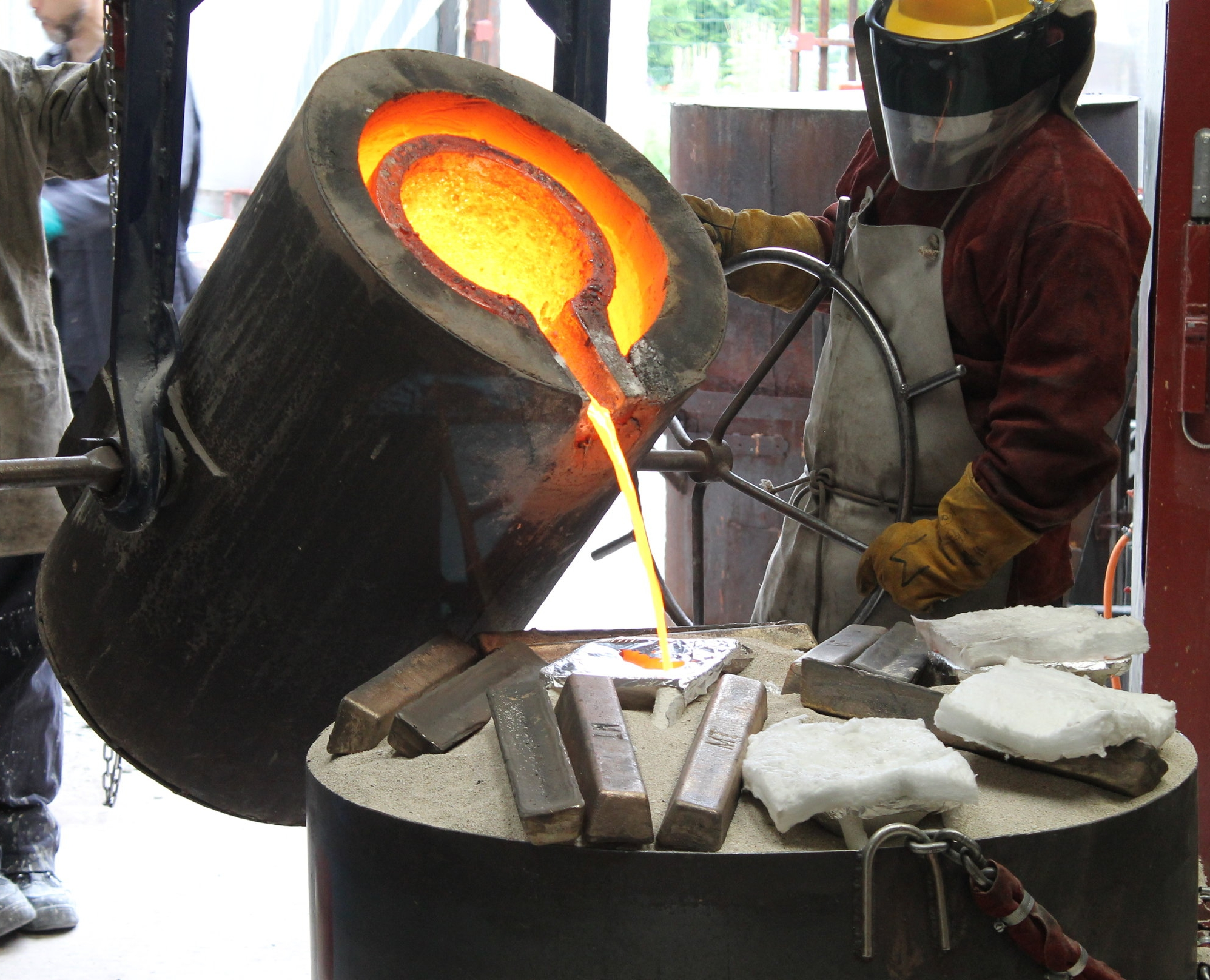Molten bronze being poured into ceramic casts