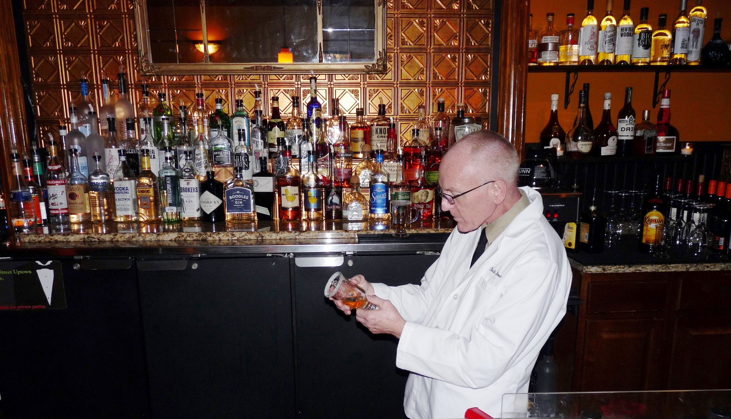 Dennis of Birch Street Uptown Lounge surveying the process thoughtfully as he caramelizes a sugar rim.