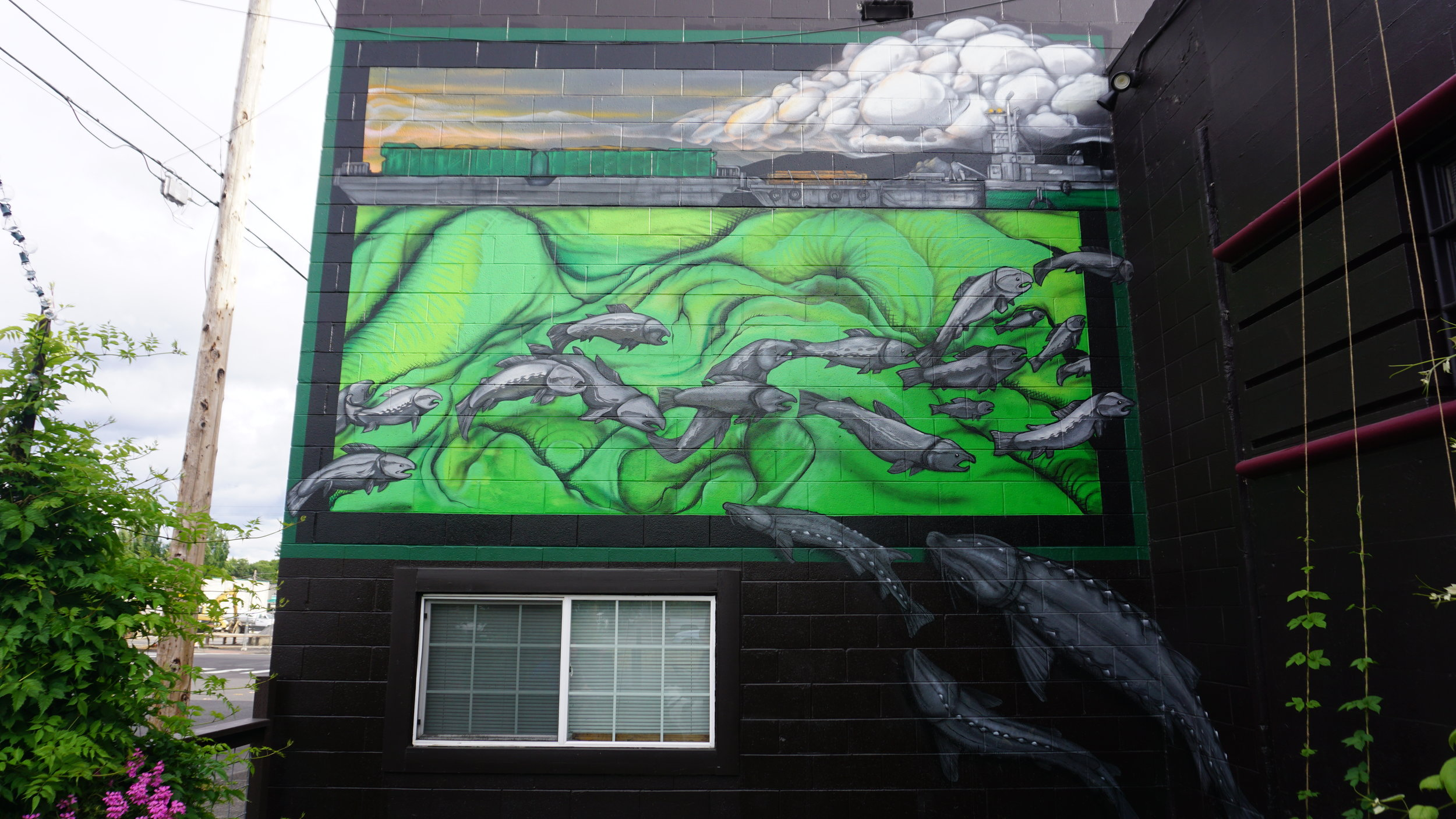the front of Cellar 55 proudly sports the 2014 first place mural entitled River Traffic created by Bret Frizelle. Viki Eierdam