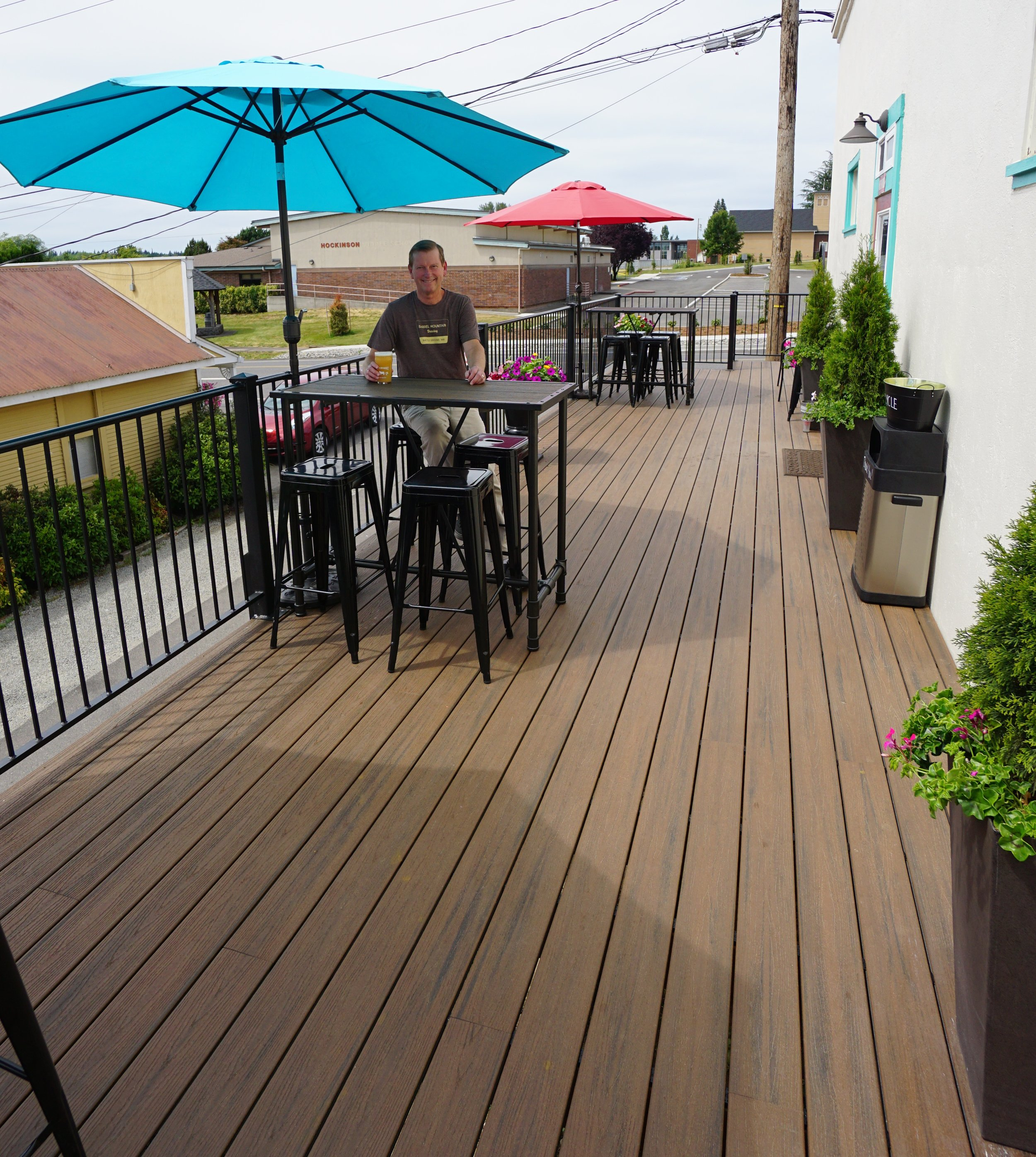 Owner Jim VanNatta sits on the back deck at Hockinson Market. Unveiled at the end of February, the back deck seats 24 comfortably and is surrounded by wrought-iron fencing while potted shrubs soften the building side of the space.Photo by Viki Eierdam