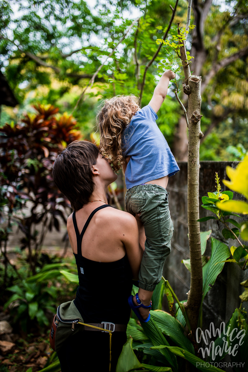 mom holding toddler looking at plant tree
