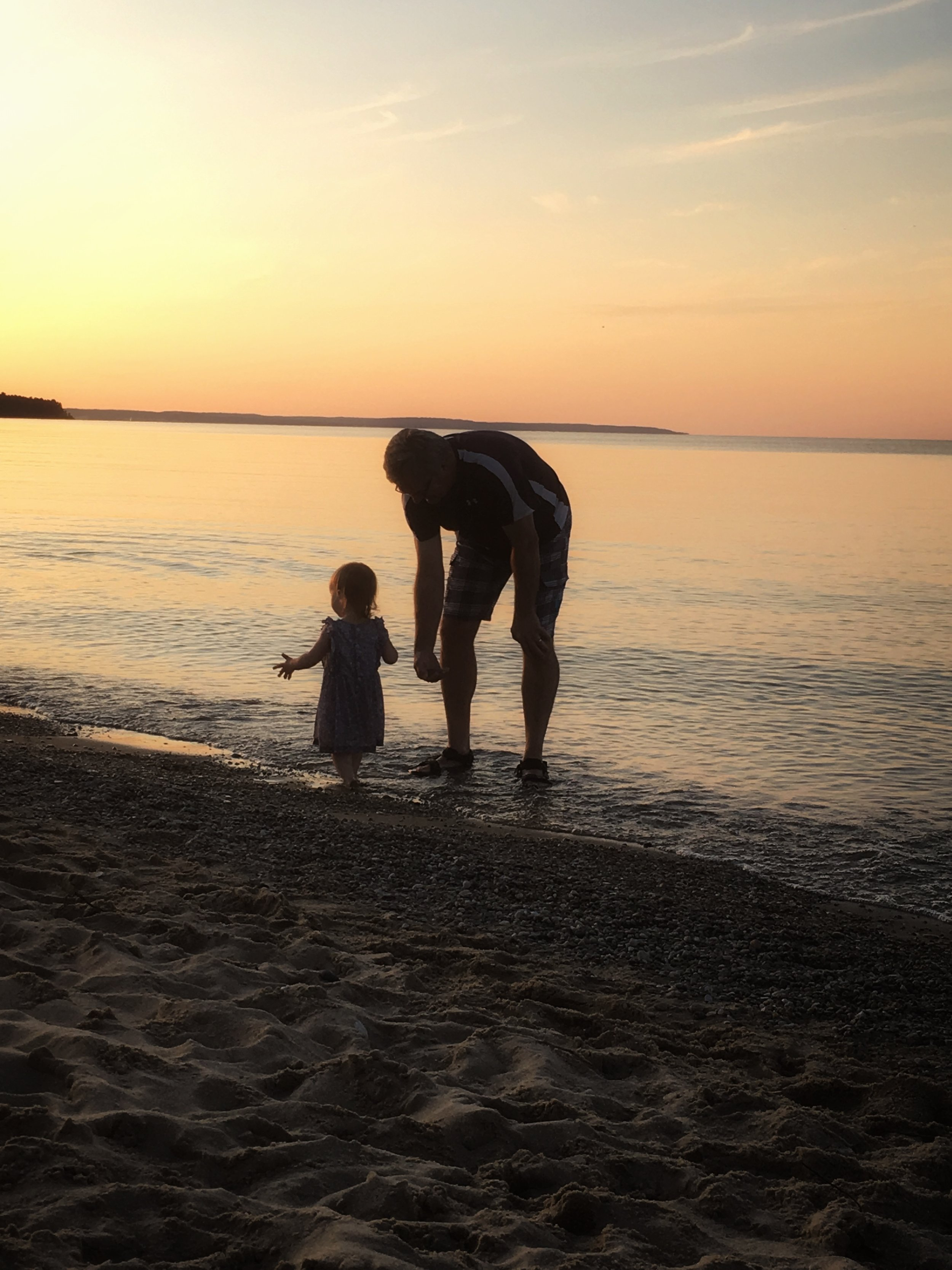 My 19 month-old daughter at the beach with her grandpa on a recent family vacation to Northern Michigan.