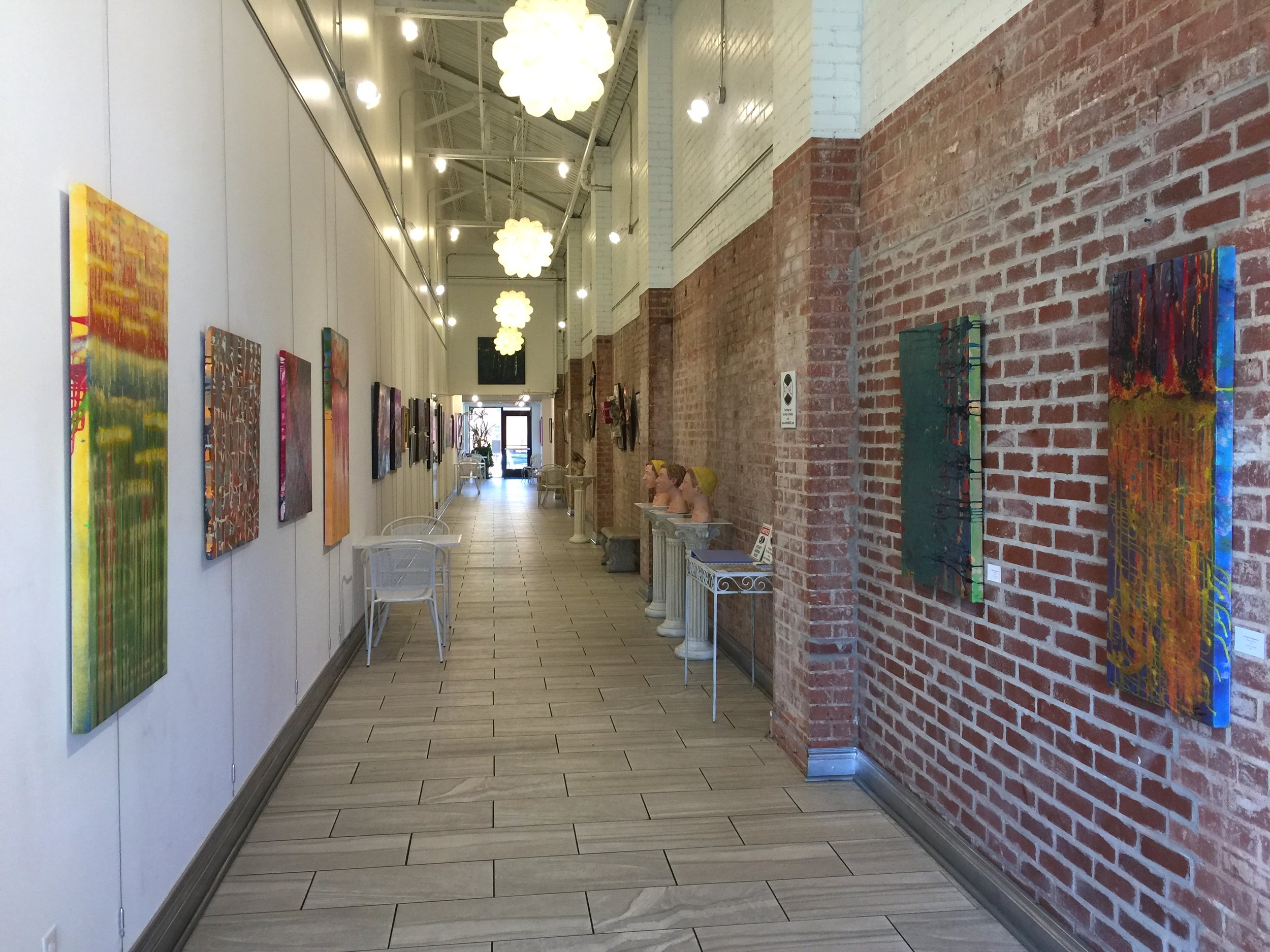 Installation view facing north, featuring paintings of Christine Partigianoni
