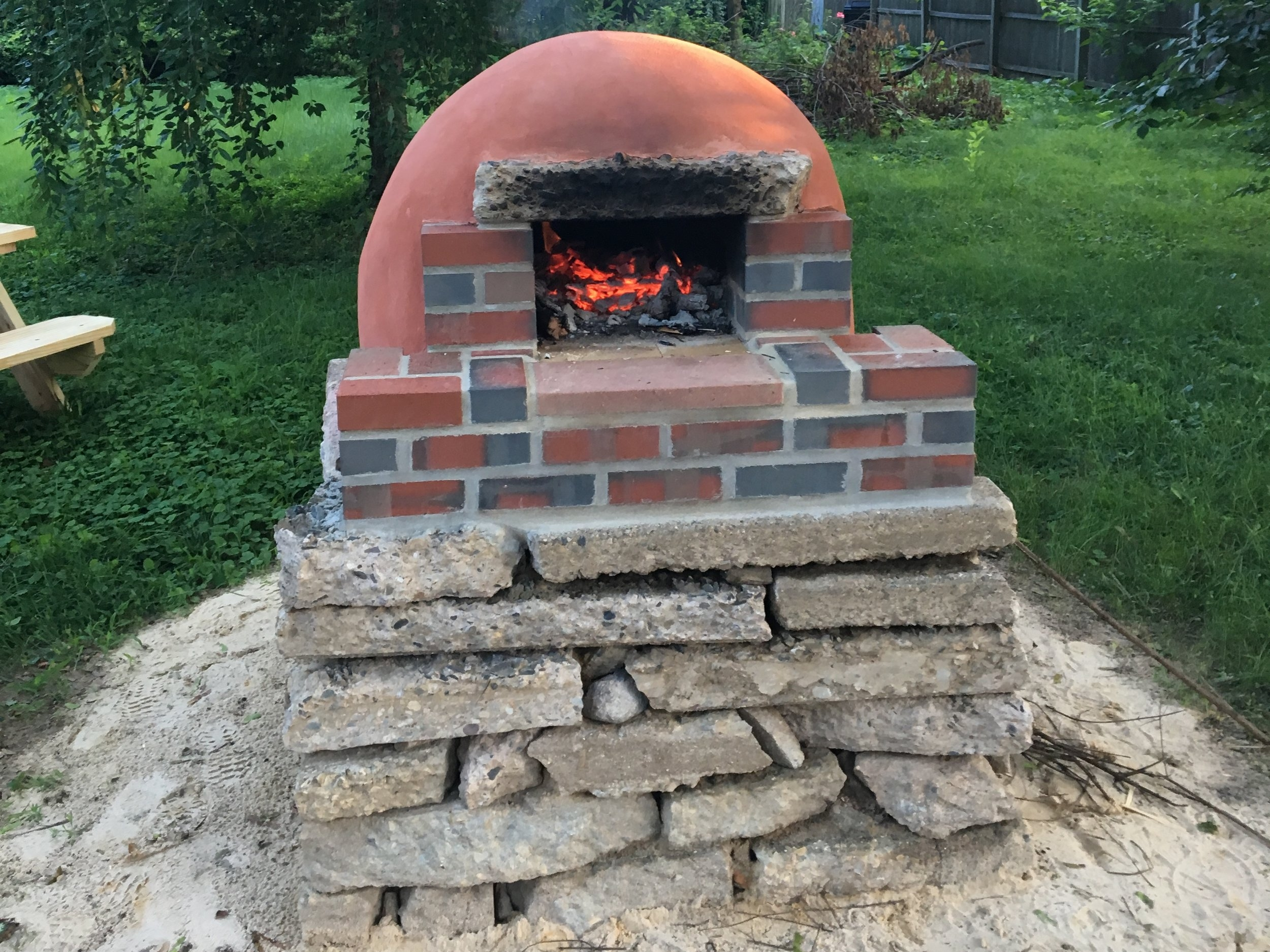 "With a mind towards recycled materials, we used ""urbanite"" for the base of this clay/masonry hybrid oven. We found a few construction sites with busted up sidewalk, and with a little sweat we had ourselves a free and durable base."