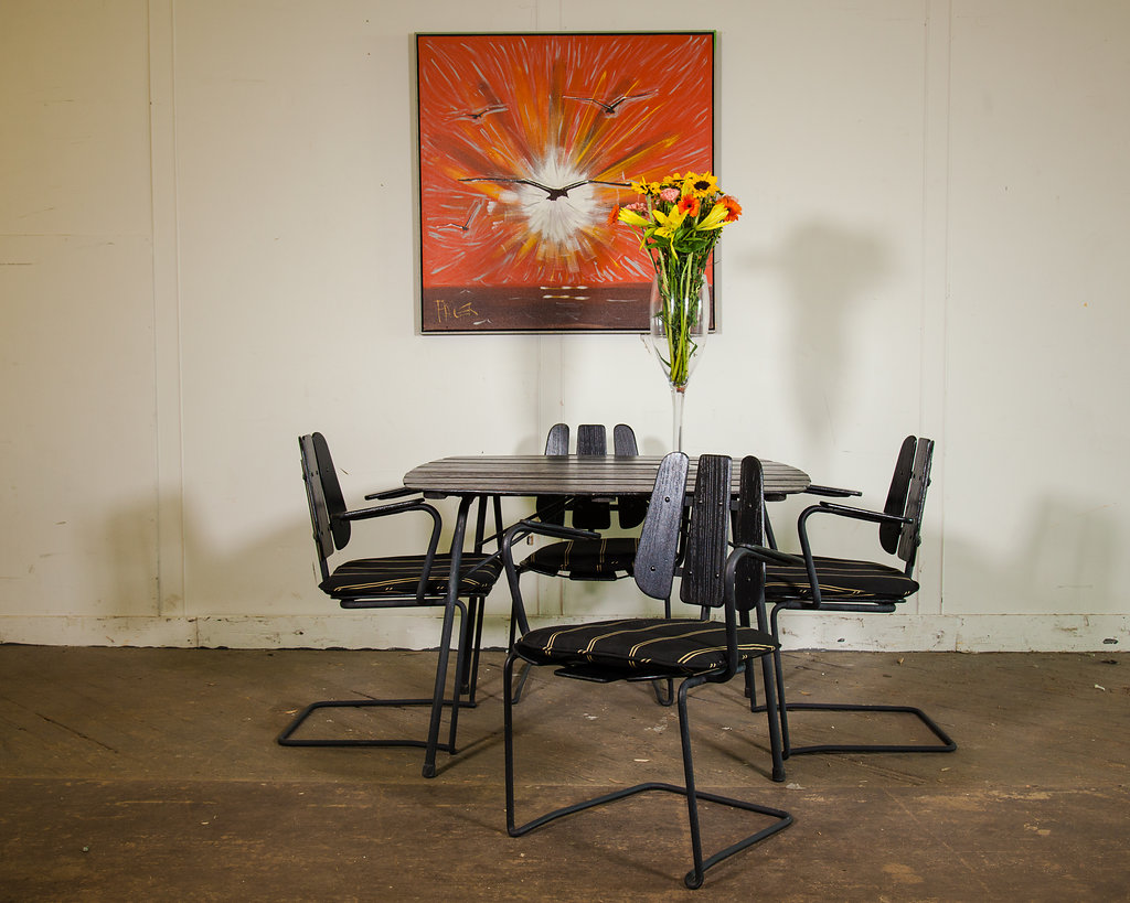 Black wooden table with four padded black/beige chairs