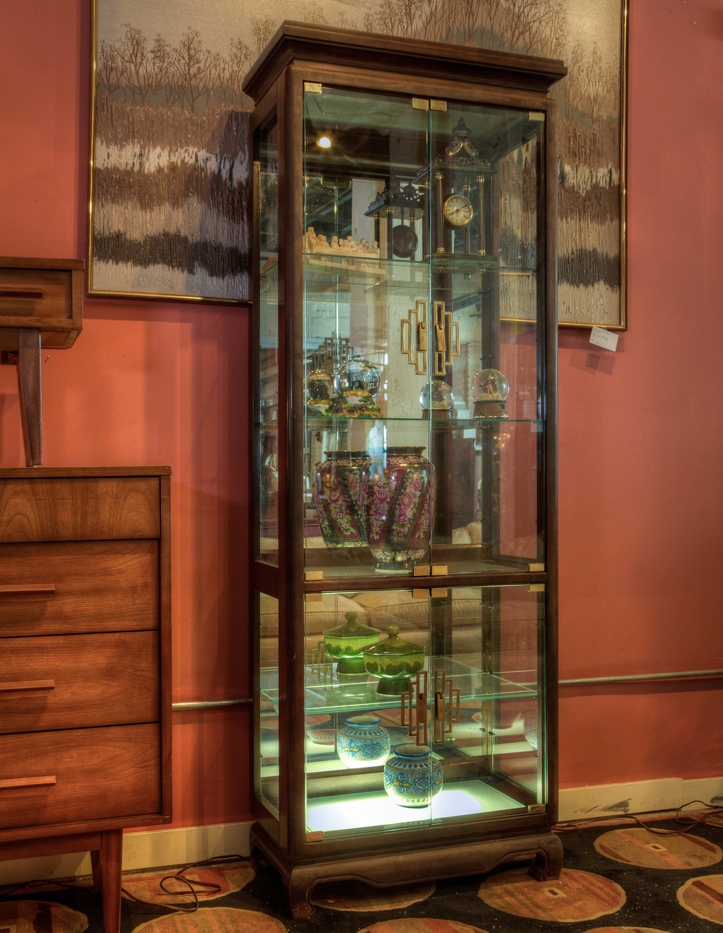 Mirrors add the illusion of light in a room. What better way to get through the post-holiday dreariness than to have a reflection with back lighting in a showcase like this one.
