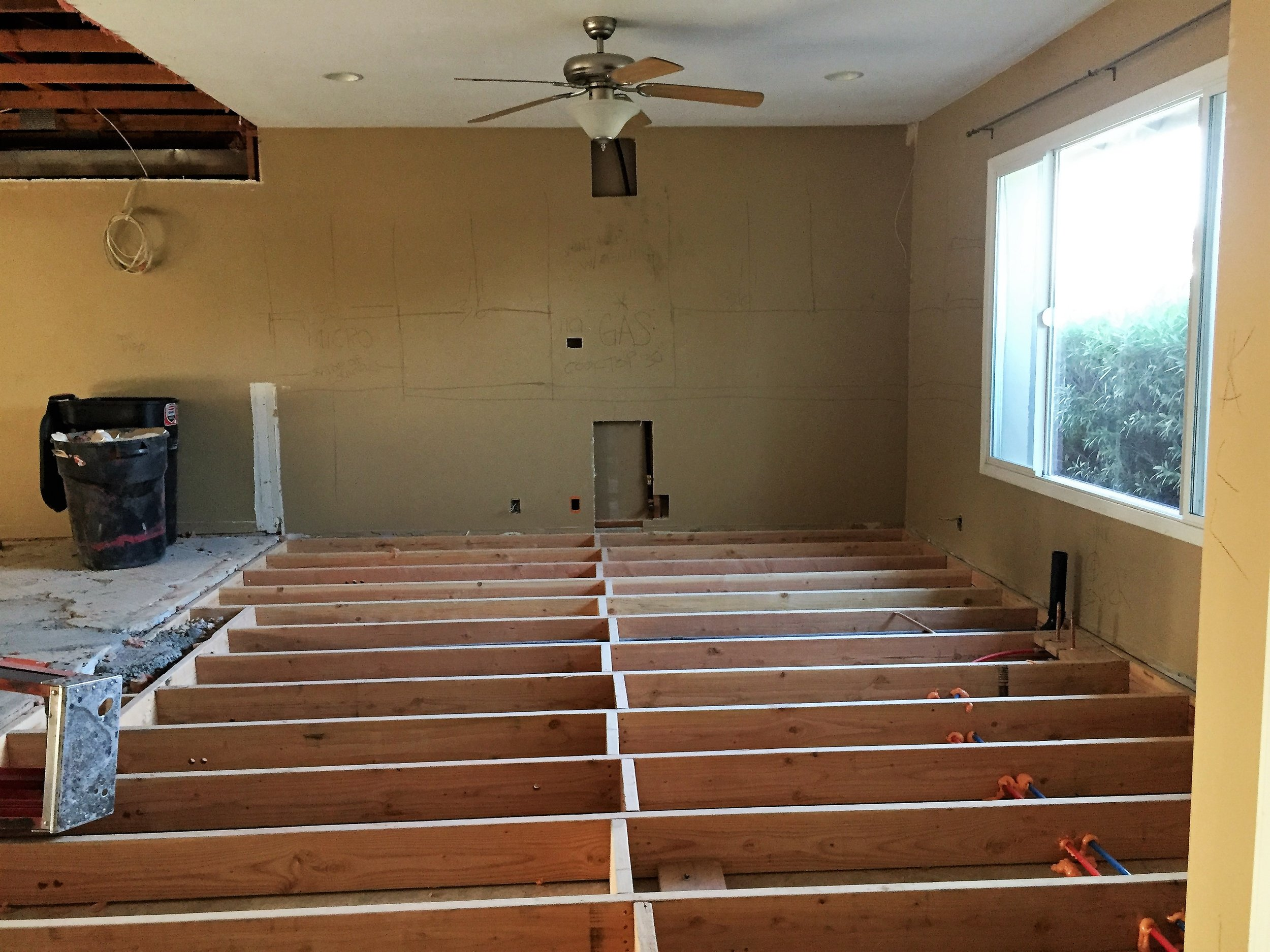 After demo: Future kitchen space - you can see the layout of cabinets, stove, oven, etc. written on the wall. The floor is being filled in!