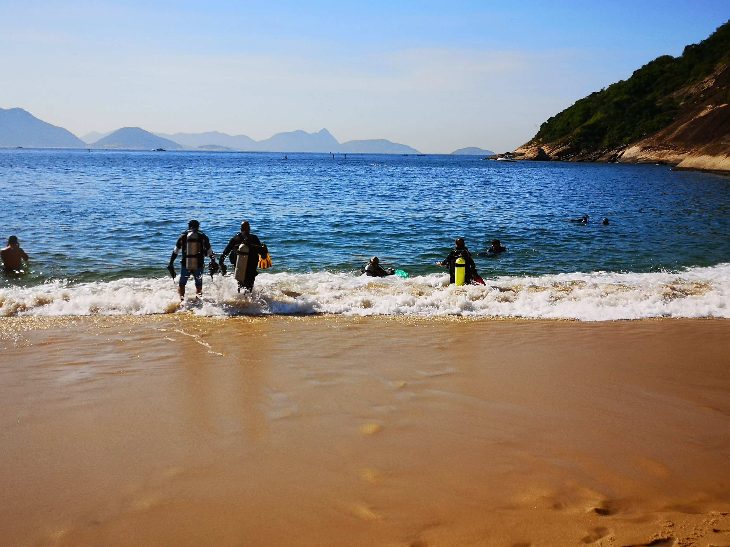 Divers entering the water at Praia Vermelha to scour for waste.