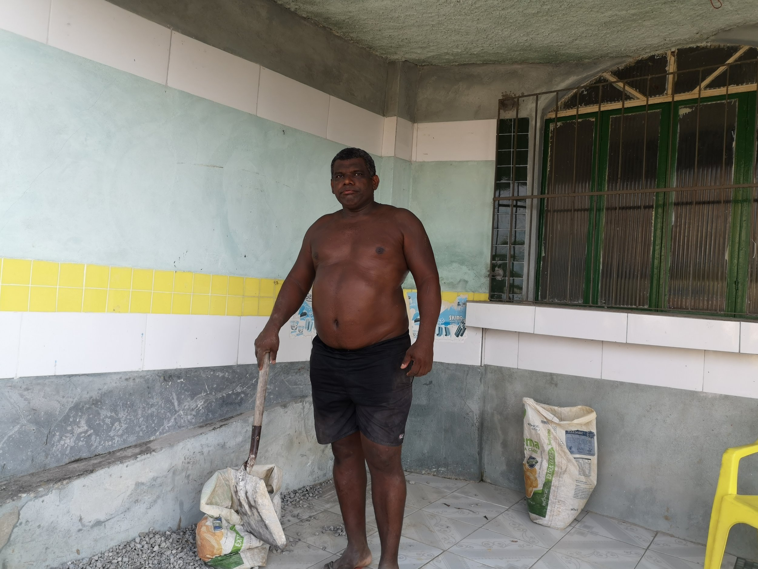 Neighbor Elias, on the porch of his house, designing his terrace with left-over tiles