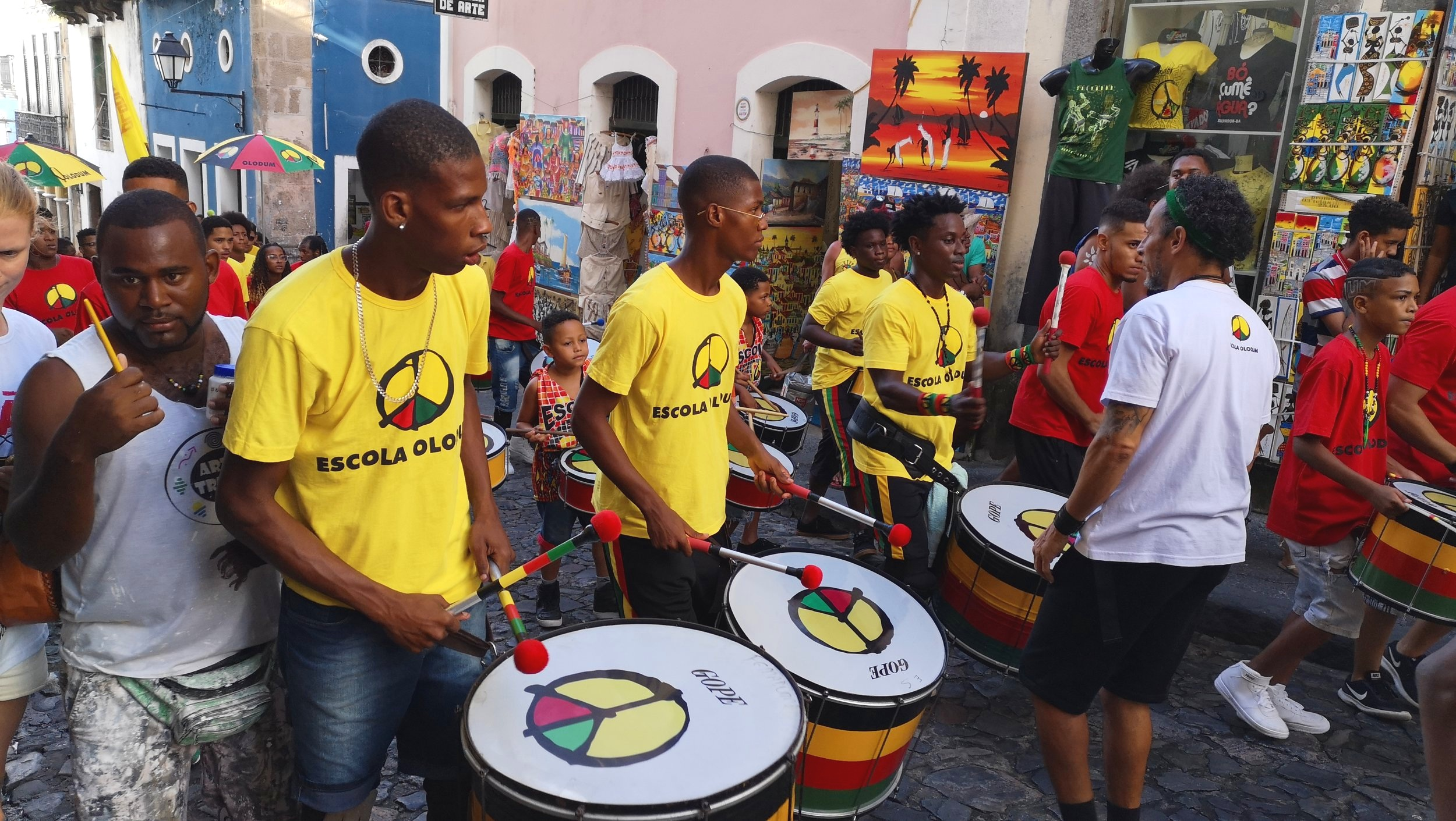 The word Olodum means 'God of Gods'. Their colourful, iconic symbol represents different elements of Afro-Brazilian culture. Black represents the dark skin color of the Afro-Brazilians and red relates to the blood that runs through our bodies. Brazil's flourishing fauna is expressed in the green and gold represents the rich African soil.